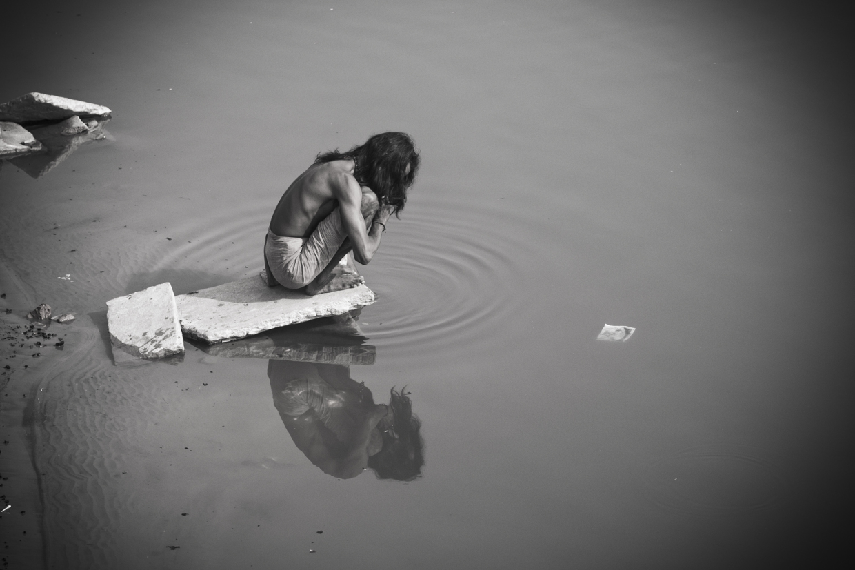A man prays by the river Ganges after his morning bath.