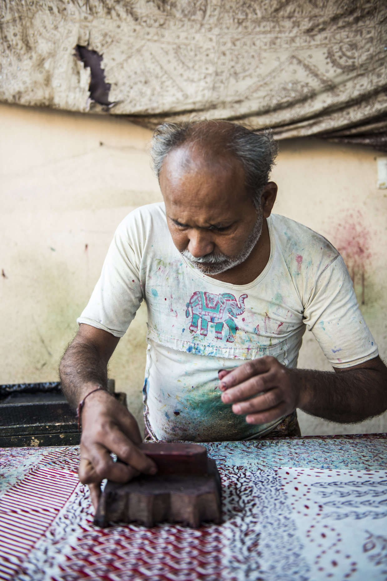 A worker paints on different symbols and designs for a completely hand made carpet.