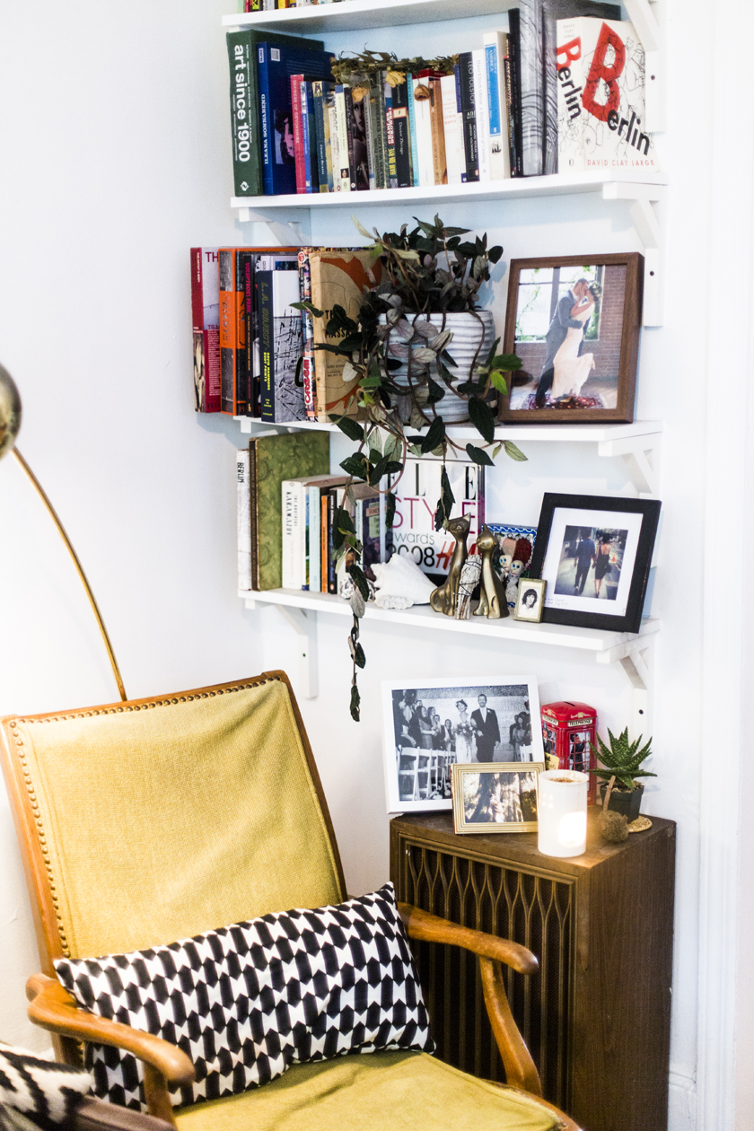 The yellow chair and gold floor lamp are both cheap vintage finds from Ebay and Craigslist. Isaac made the simple shelves using wood cut at Home Depot and painting them white.