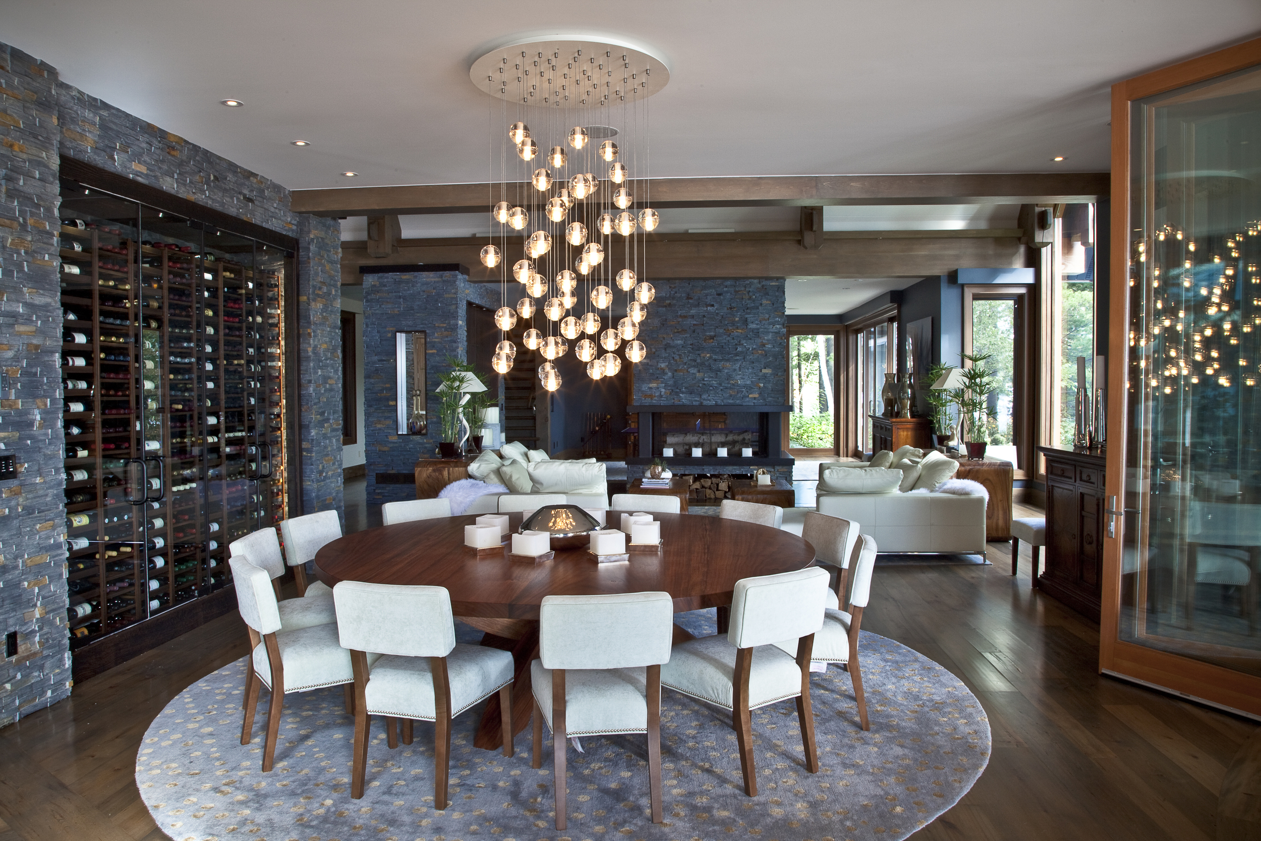 dining room with light bulb chandelier above a wooden table and dining chairs
