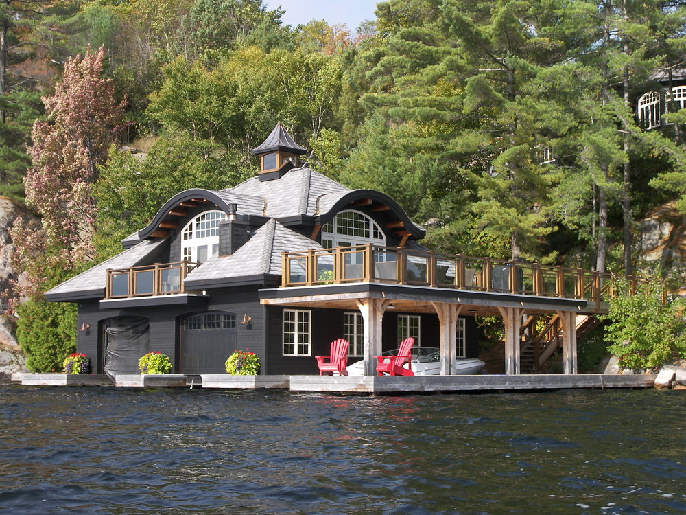 large custom boathouse with grey exterior on the edge of a lake