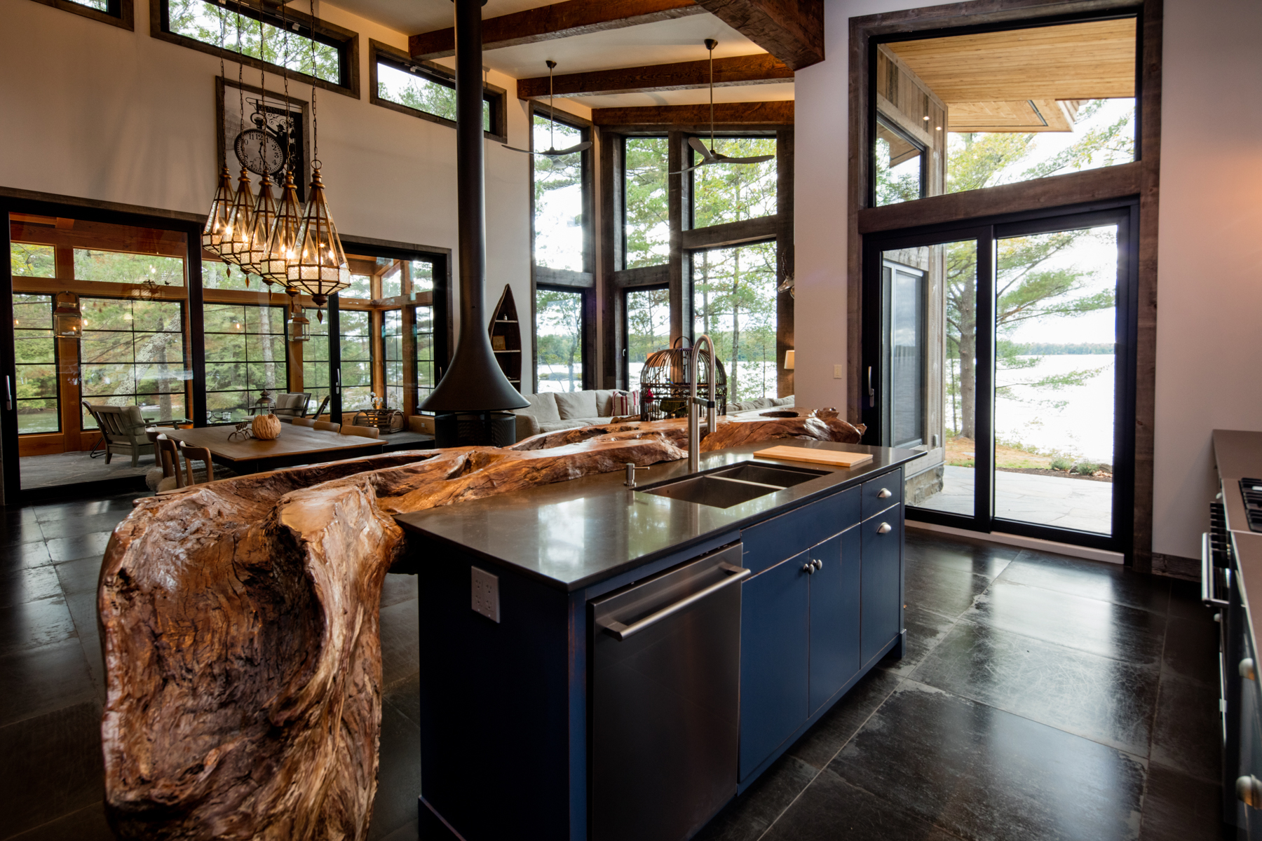 naturally lit open concept kitchen with and island and natural wood table