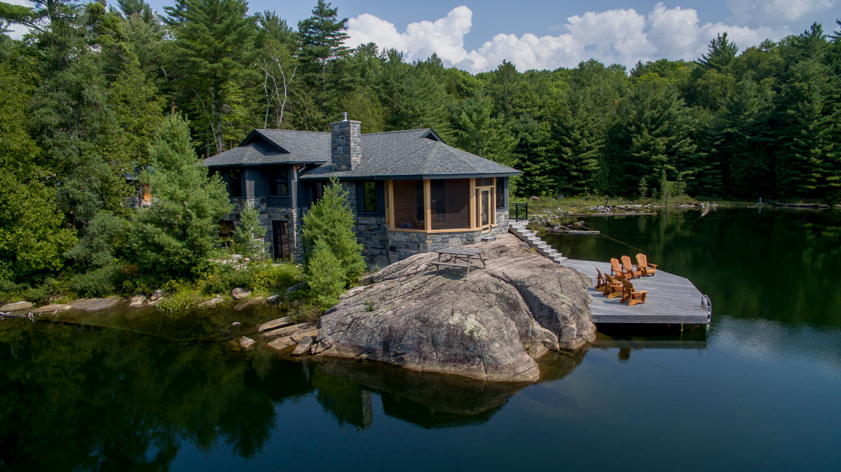 Cottage with grey stone exterior with wooden patio seating on the edge of a lake surrounded by trees.
