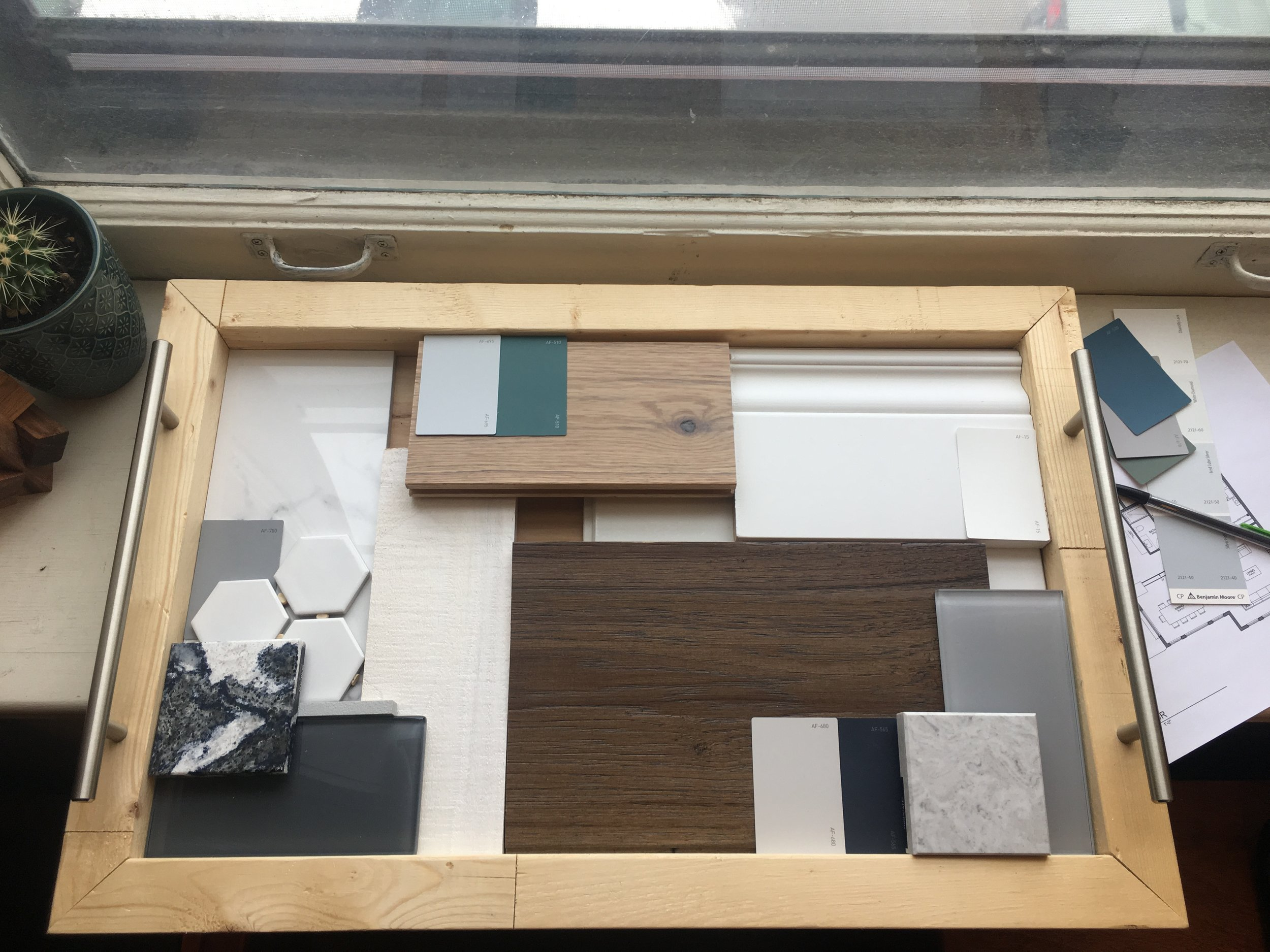 box of materials with samples of tiles, wood, marble, baseboard mold, and colour samples
