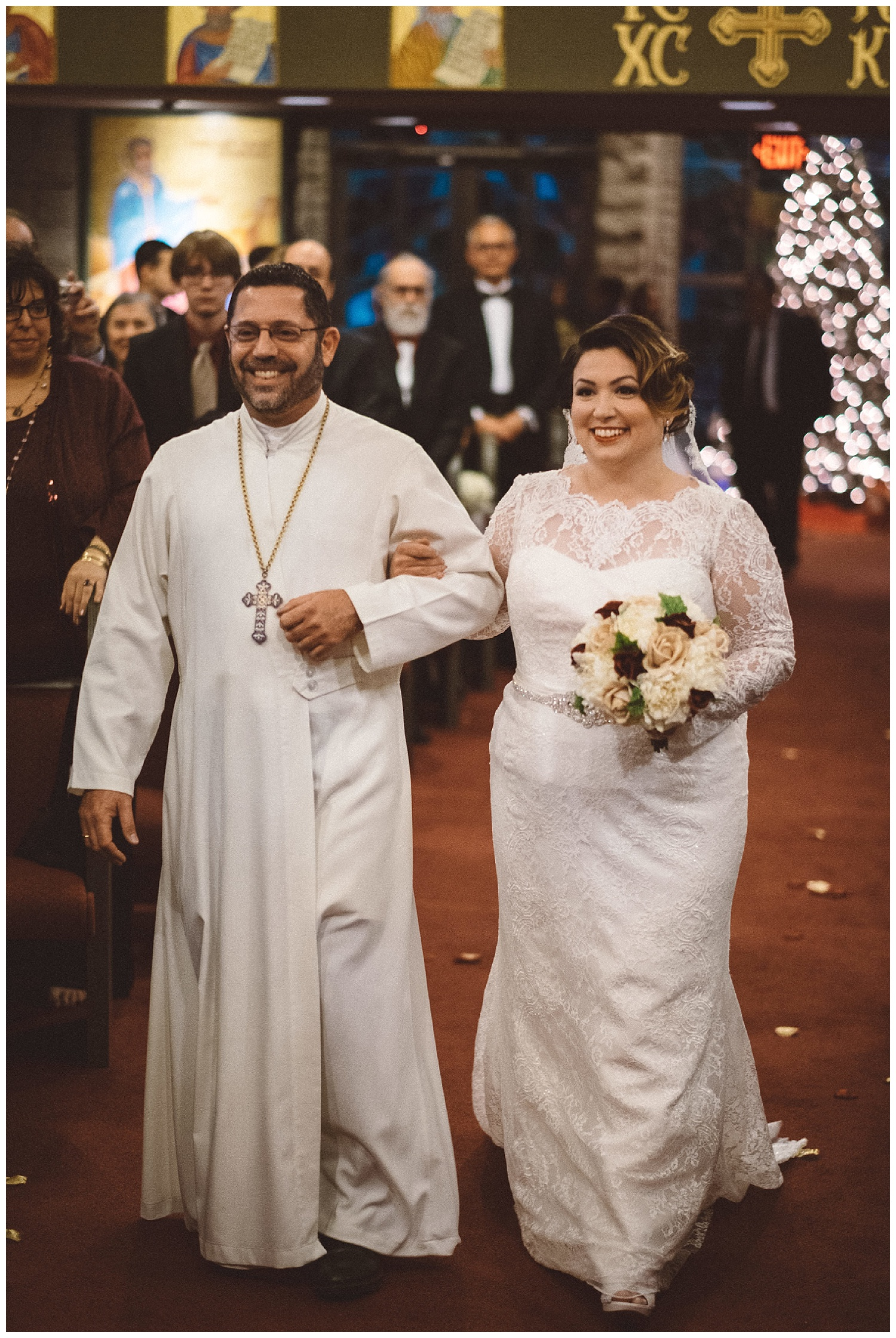 Bride walks down the aisle with Fr Michael Nasser at St Luke's Orthodox Church