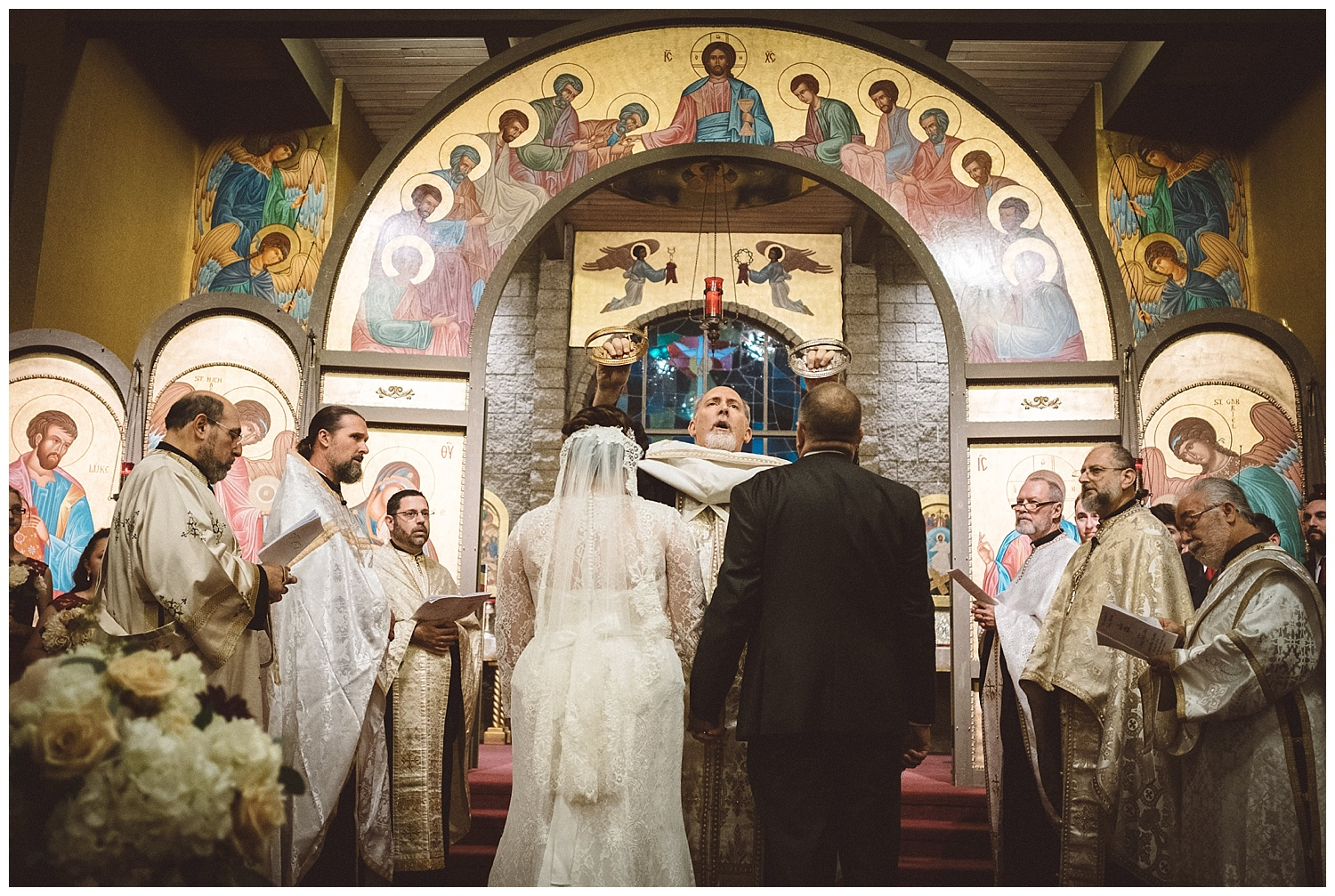 Orthodox priest Fr. Michael Tassos places wedding crowns on bride and groom