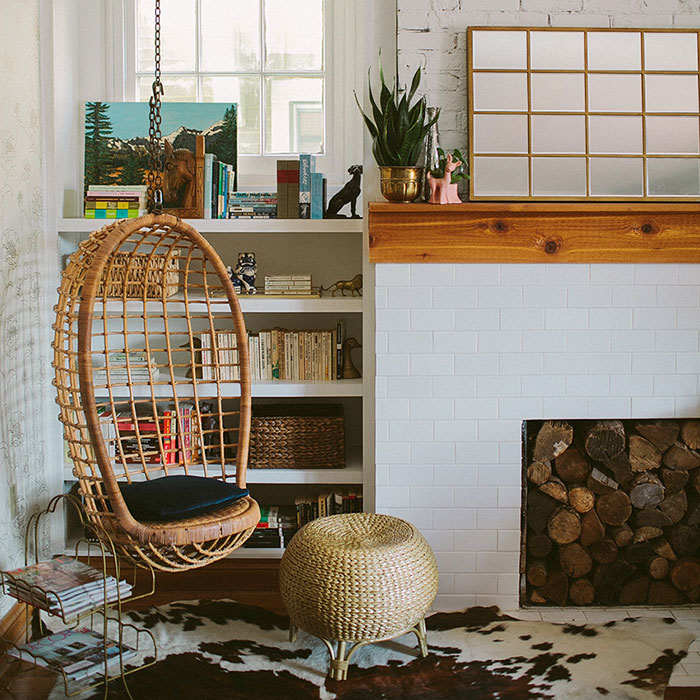 If you don't have a cowhide, no worries! Just add a blanket or floor rug to your space so you can have something soft to rest your feet on as you turn the next page. This hanging chair could use an extra cushion or two, but there's something about lounging in a floating chair that makes the nook experience a little more magical. And the earthy tones of the wood accents (obviously the logs in the fireplace cutout) mixed with pops of color from books and knick-knacks create a bit of character that sets it apart from typical room corners.