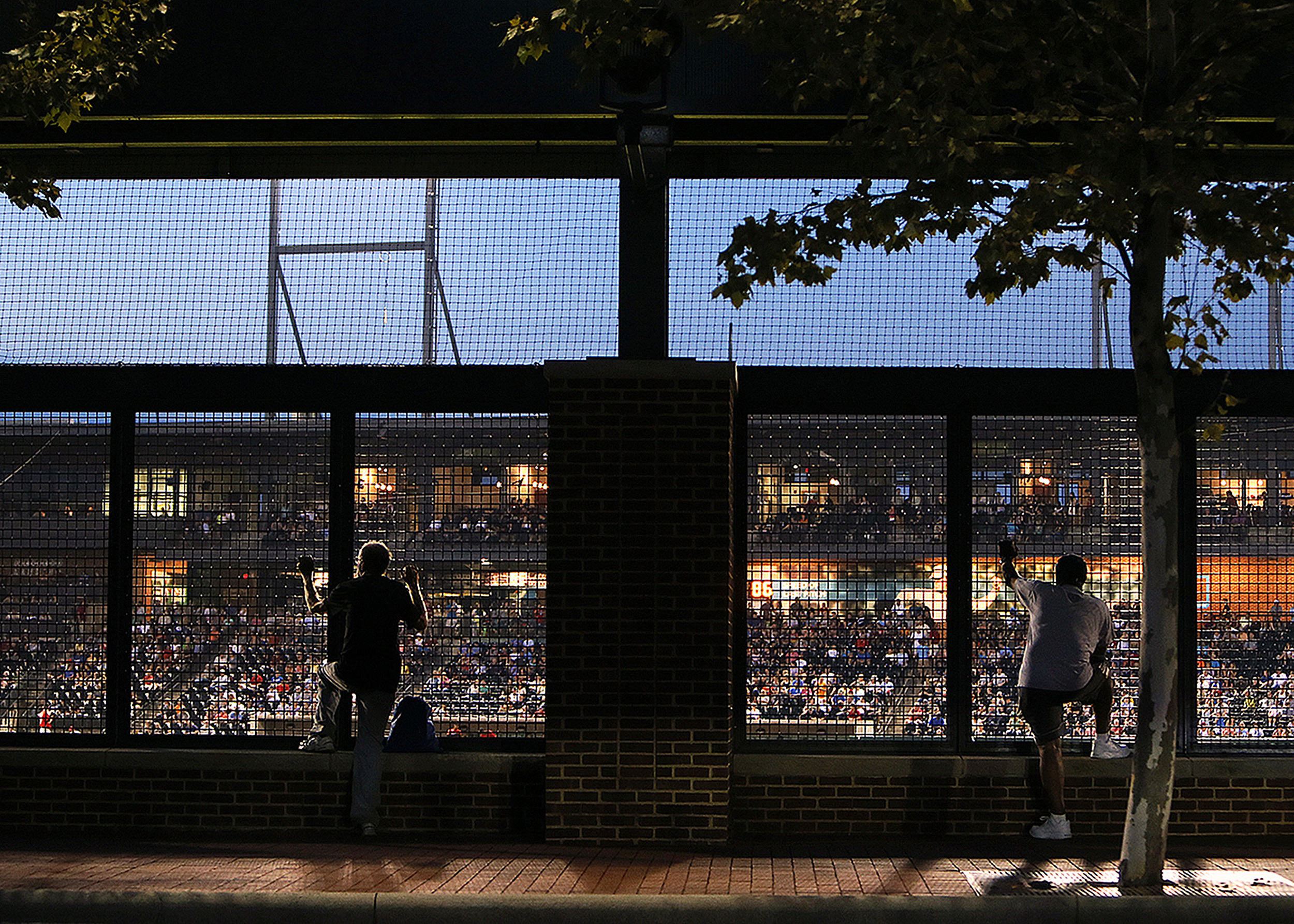A few fans passing by watch from the street as the Columbus Clippers take on the Indianapolis Indians at Huntington Park in Columbus, Ohio, Monday, August 25, 2014.