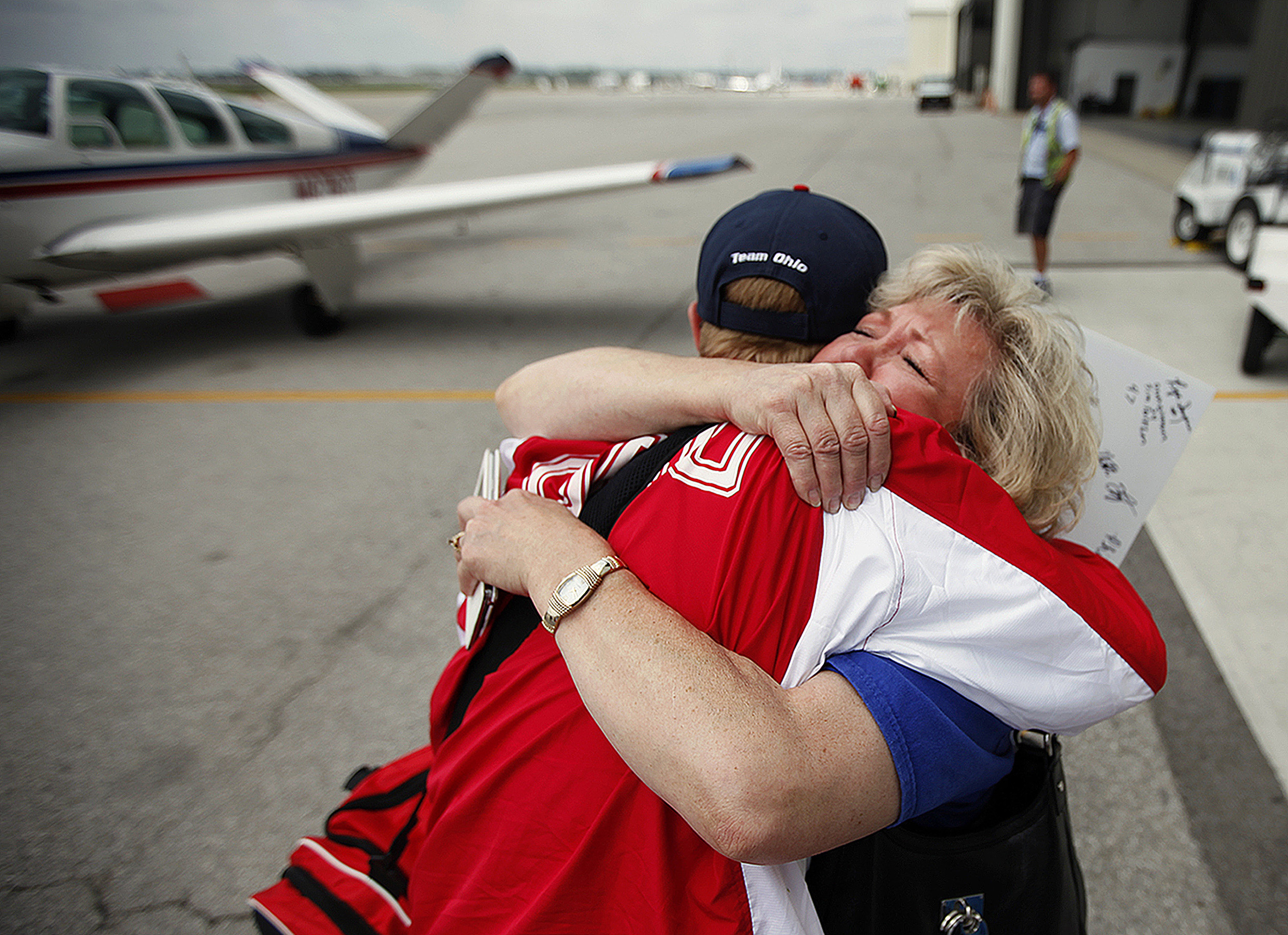 Cory Anatangelo, of Ohio's gold medal-winning Special Olympics softball team, embraces mother Pam Anatangelo, who sheds tears of joy as she welcomes him home from New Jersey, at the Lane Aviation terminal of Columbus International Airport in Ohio, Saturday, June 21, 2014. The softball team won a gold medal.