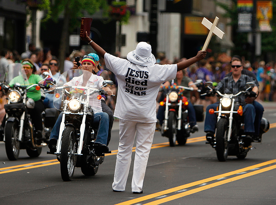 A single protestor is outnumbered by an oncoming group of the parade's motorcyclists during the annual Stonewall Columbus LGBT pride parade, in downtown Columbus, Ohio, June 21, 2014.