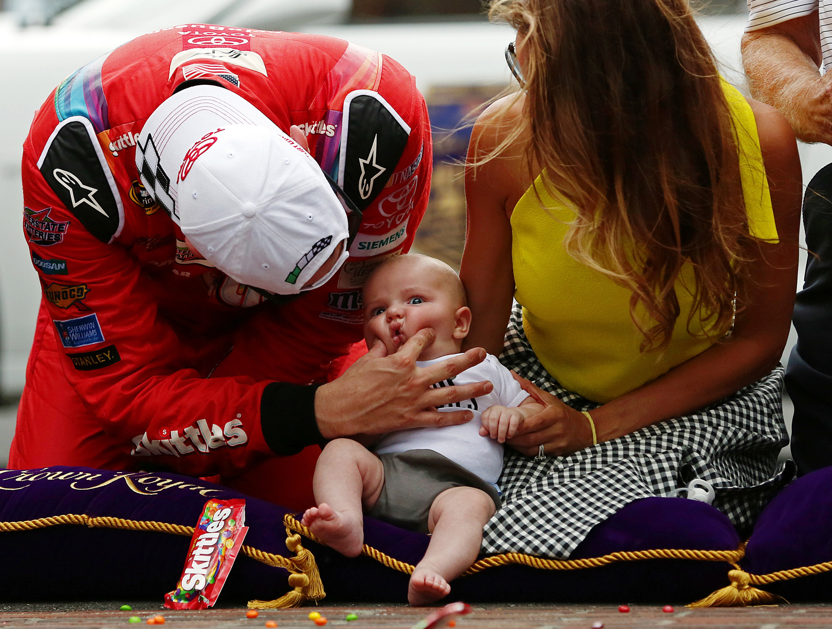 Sprint Cup Series driver Kyle Busch (18) squeezes the cheeks of son Brexton Locke next to wife Samantha at the finish line bricks after winning the Jeff Kyle 400, Indianapolis Motor Speedway, Sunday,  July 26, 2015, Indianapolis, Ind.