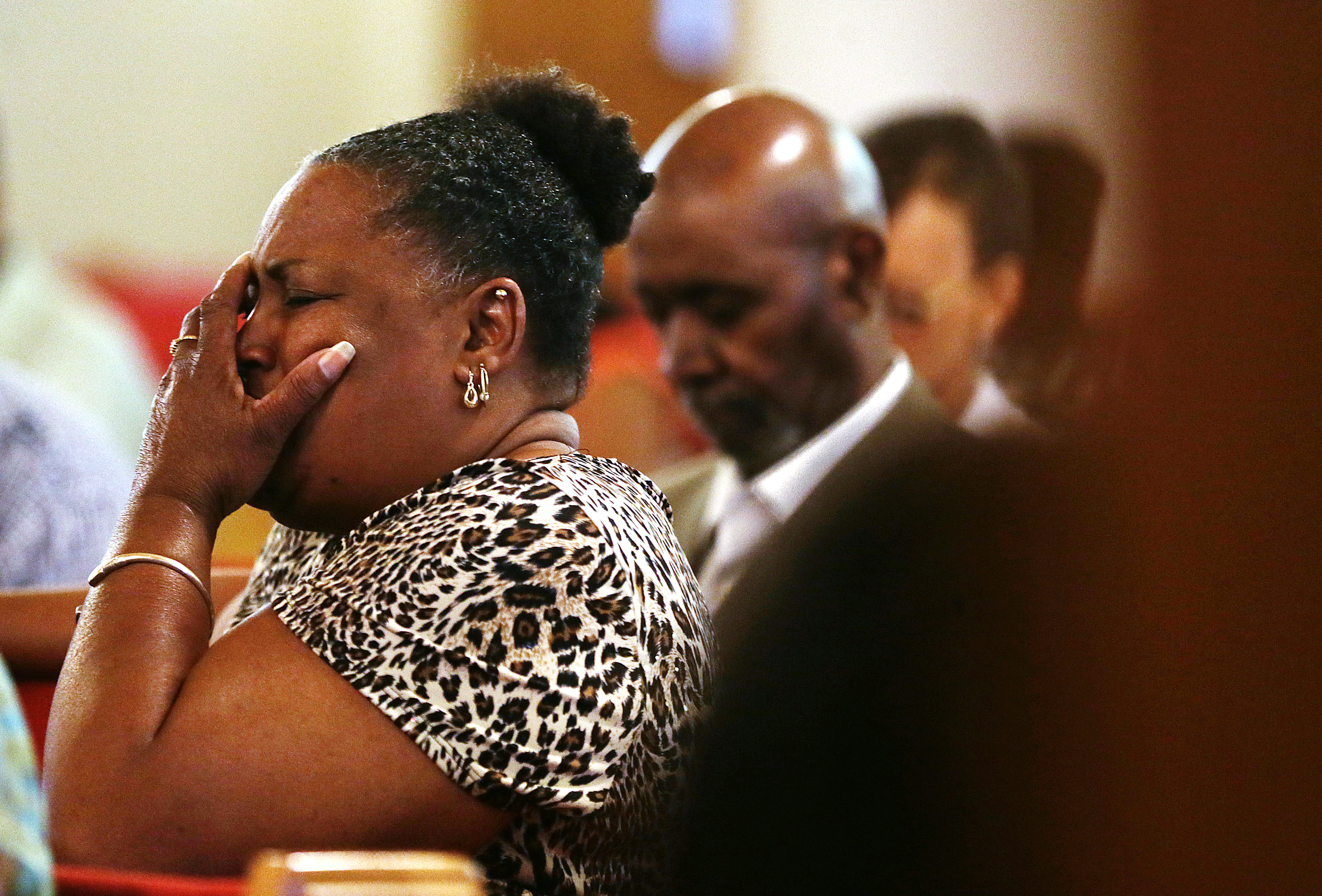 On the day following the Charleston church shooting in South Carolina, Bonnie Collins, of Brownsburg, Ind., holds her head in grief at the start of a vigil service held at St. John African Methodist Episcopal church for the shooting's victims, Indianapolis, Ind., June 18, 2015.