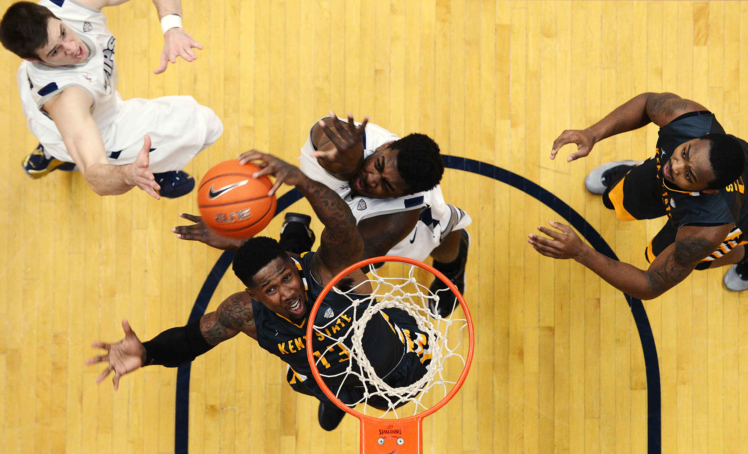 (Center) Kent State red shirt senior guard Derek Jackson takes a shot, under defense from University of Akron sophomore center Isaiah Johnson at the James A. Rhodes Arena in Akron, Ohio, Tuesday, February 10, 2015. Kent lost to Akron, 61-52.