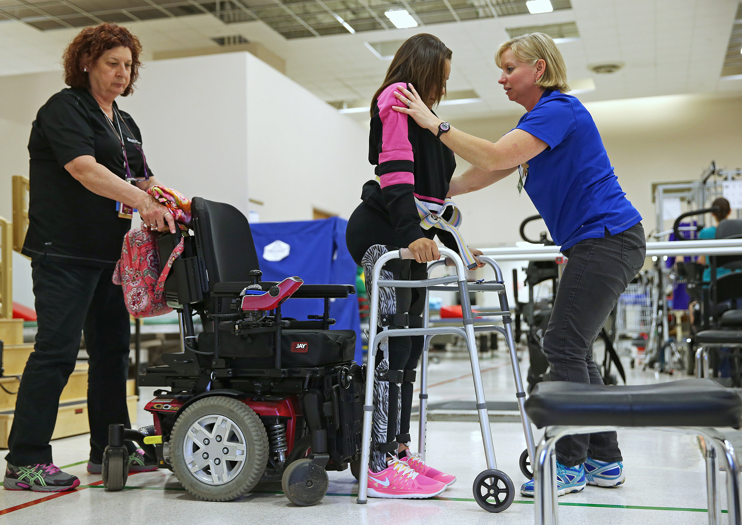 Physical therapist Kim Deckman (right) helps Macy Huff (center) into leg braces before a session at the Rehabilitation Hospital of Indiana in May. Huff attended the rehabilitation sessions twice a week in preparation for hight school graduation. Each session, she walked increasing distances with Deckman's assistance, leg braces and a walker.