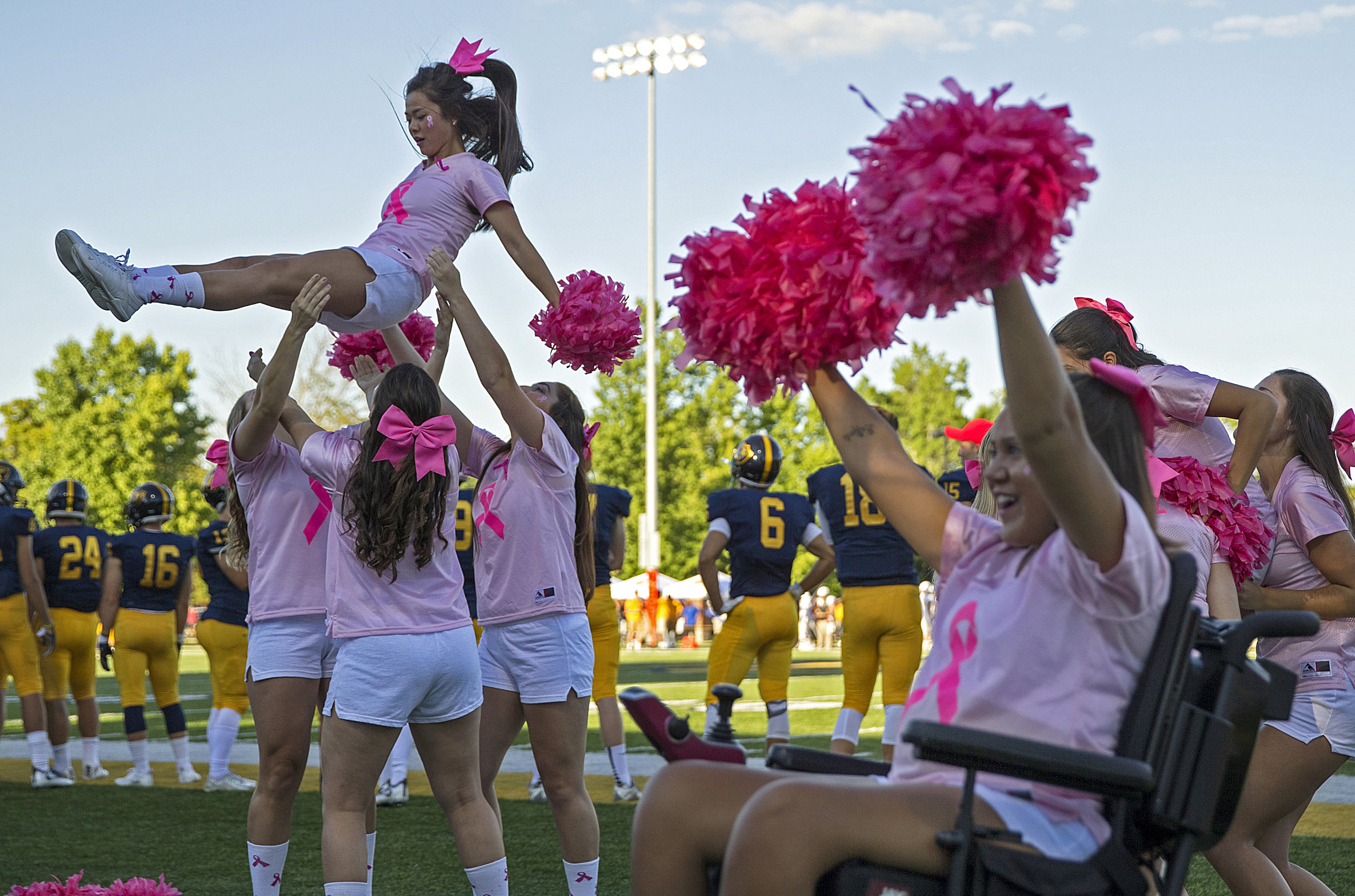 At right, Macy cheers while a other cheerleaders complete a stunt during the first game of the season at Franklin College. It took a while after her injury for Huff to realize cheerleading is not about stunts and tumbling, but instead about optimism, leadership and being a role model for young girls.