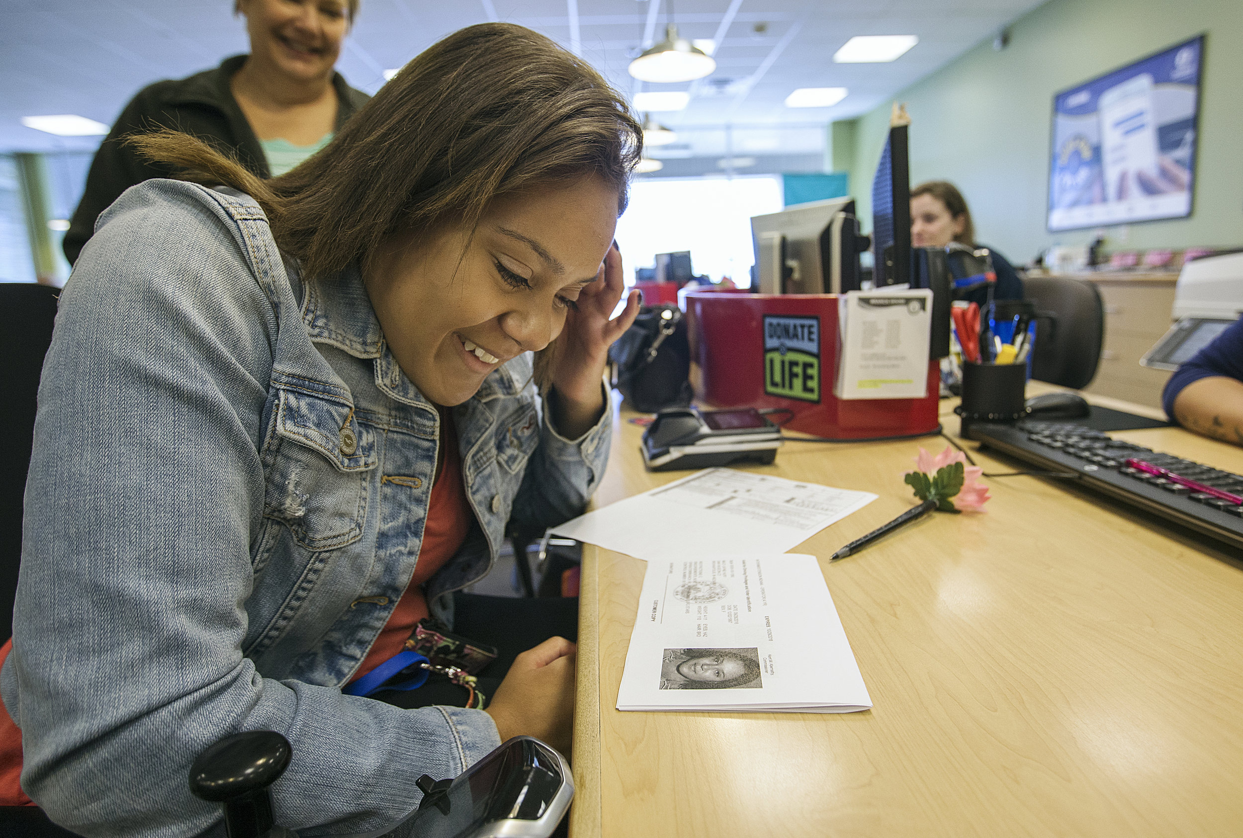 Macy's face lights up as she receives a temporary copy of her driver's license. Earning her license is the next step in Macy earning her independence.