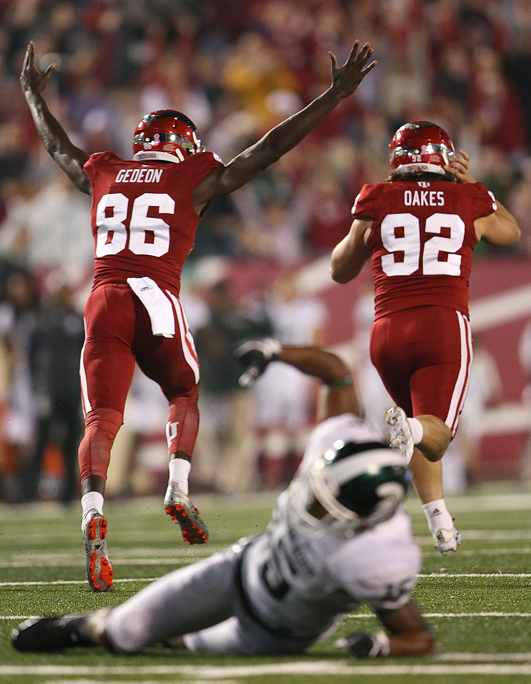 Indiana Hoosiers kicker Griffin Oakes (92) kicks a field goal to defeat Michigan State 24-21 in overtime, Bloomington, Ind., Saturday, October 1, 2016. Oakes and Indiana Hoosiers punter Joseph Gedeon (86) celebrate as Michigan State Spartans linebacker Andrew Dowell (5) pounds the field in the foreground.