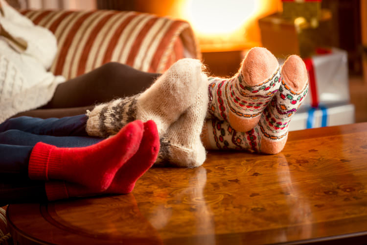 Closeup conceptual shot of family warming feet at fireplace in fuzzy socks.jpg