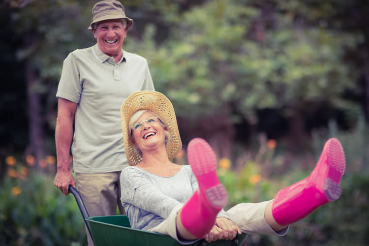 Happy elderly couple playing with a wheelbarrow.jpg