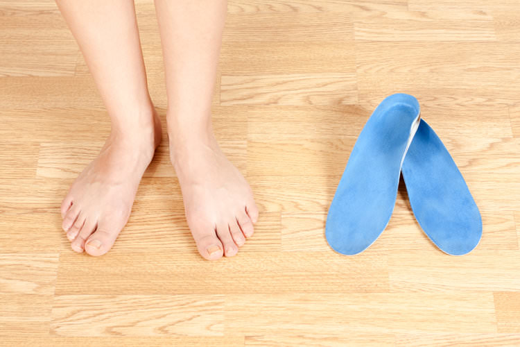 person standing next to a pair of insoles.jpg