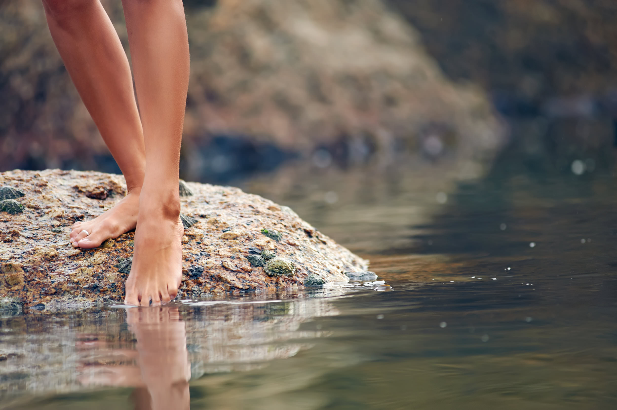 female dipping toe into water while on a rock.jpg