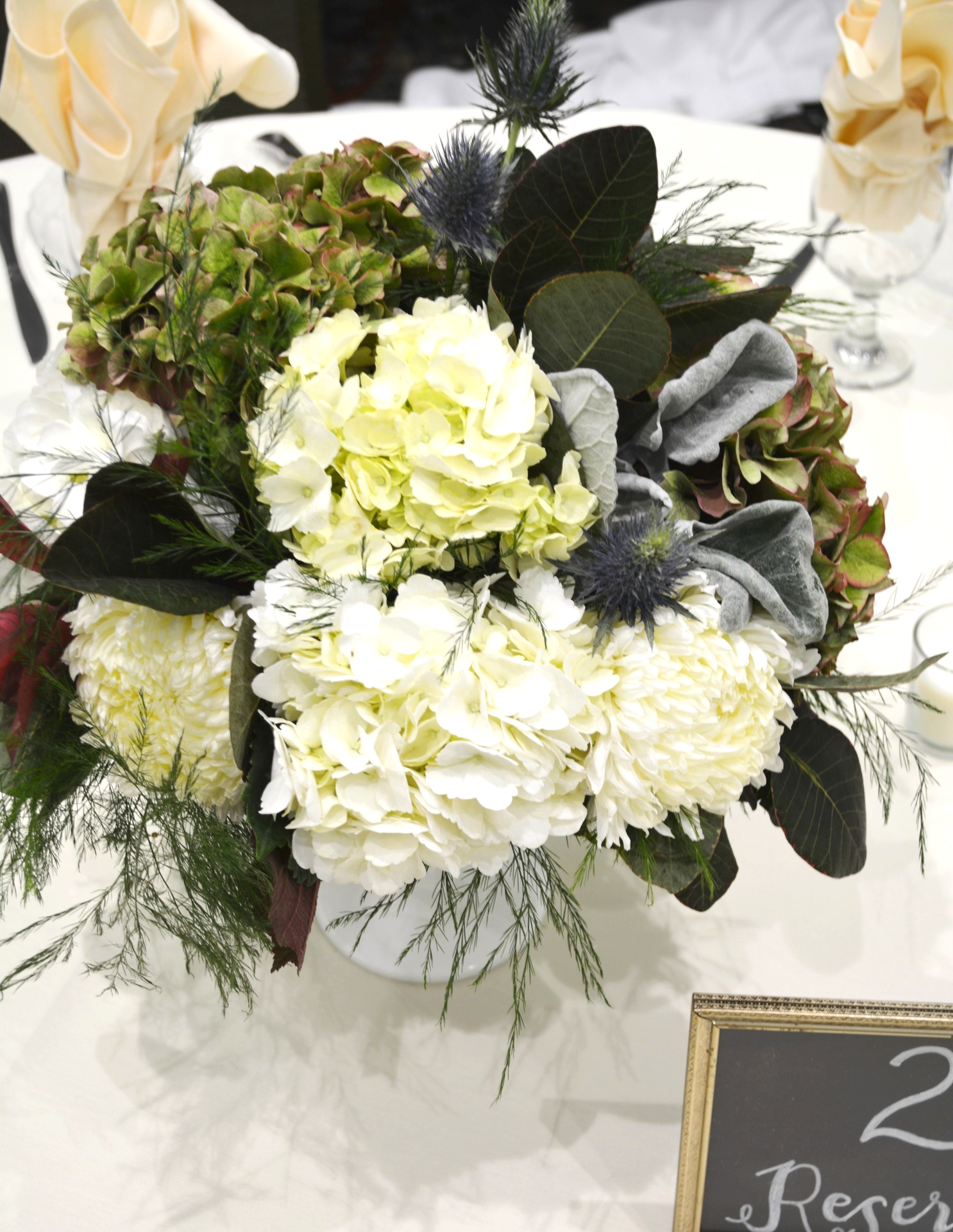 Vintage milk glass compotes mounded with tree fern, purple smoke leaf, hydrangeas, football mums and thistle
