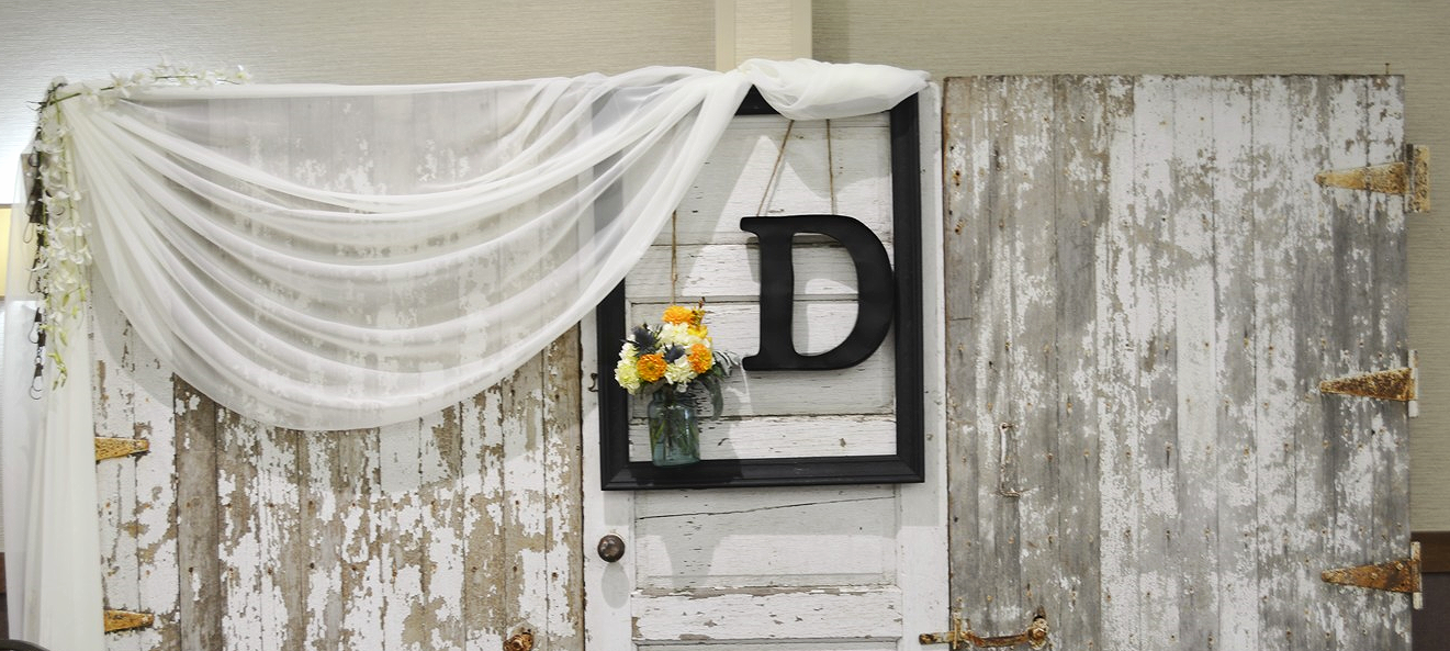 Barn door backdrop with an asymmetrical drape and other decor incorporated.