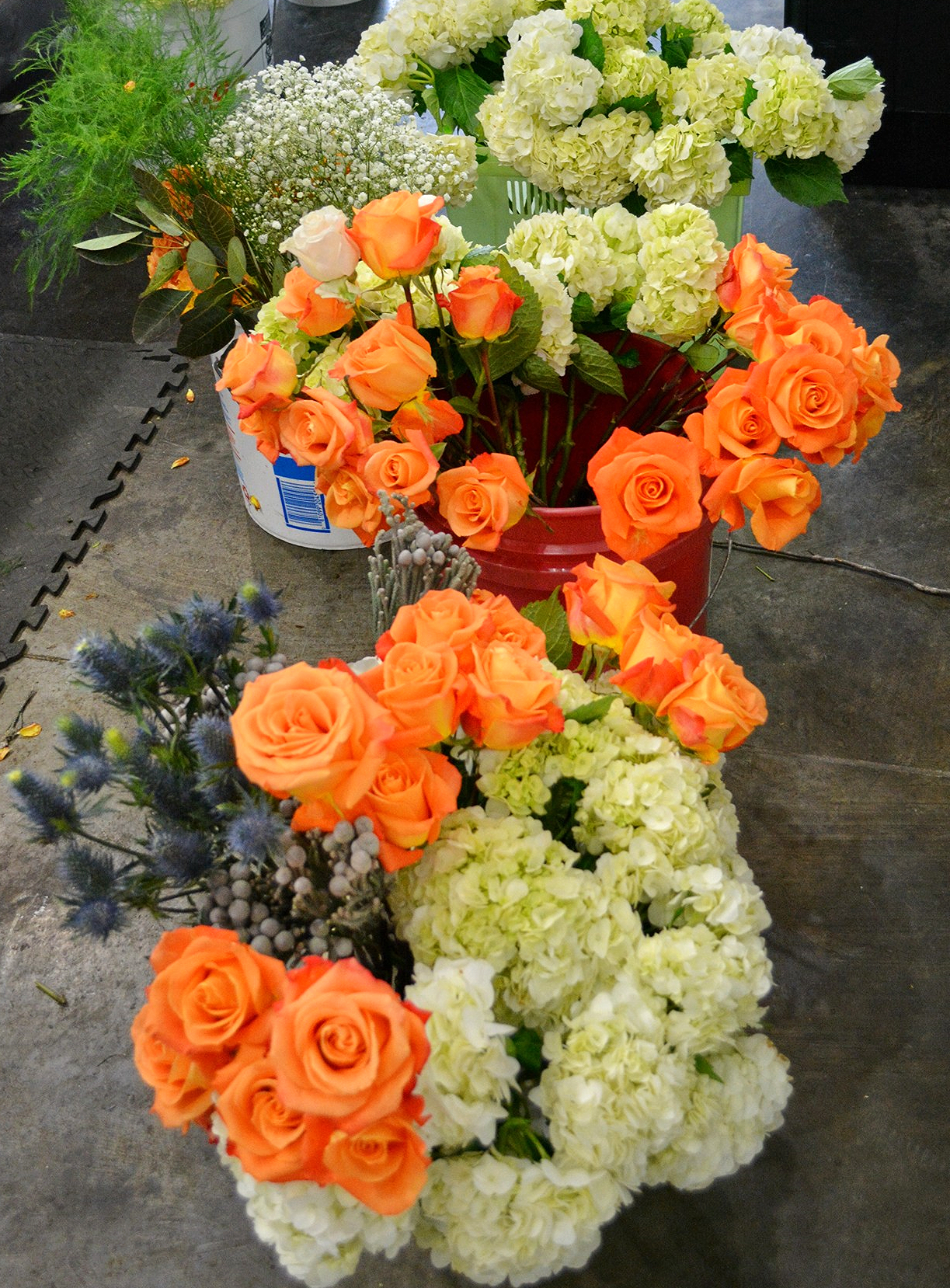 Buckets of lush hydrangeas, tangerine orange roses, thistle, berries, orchids and more