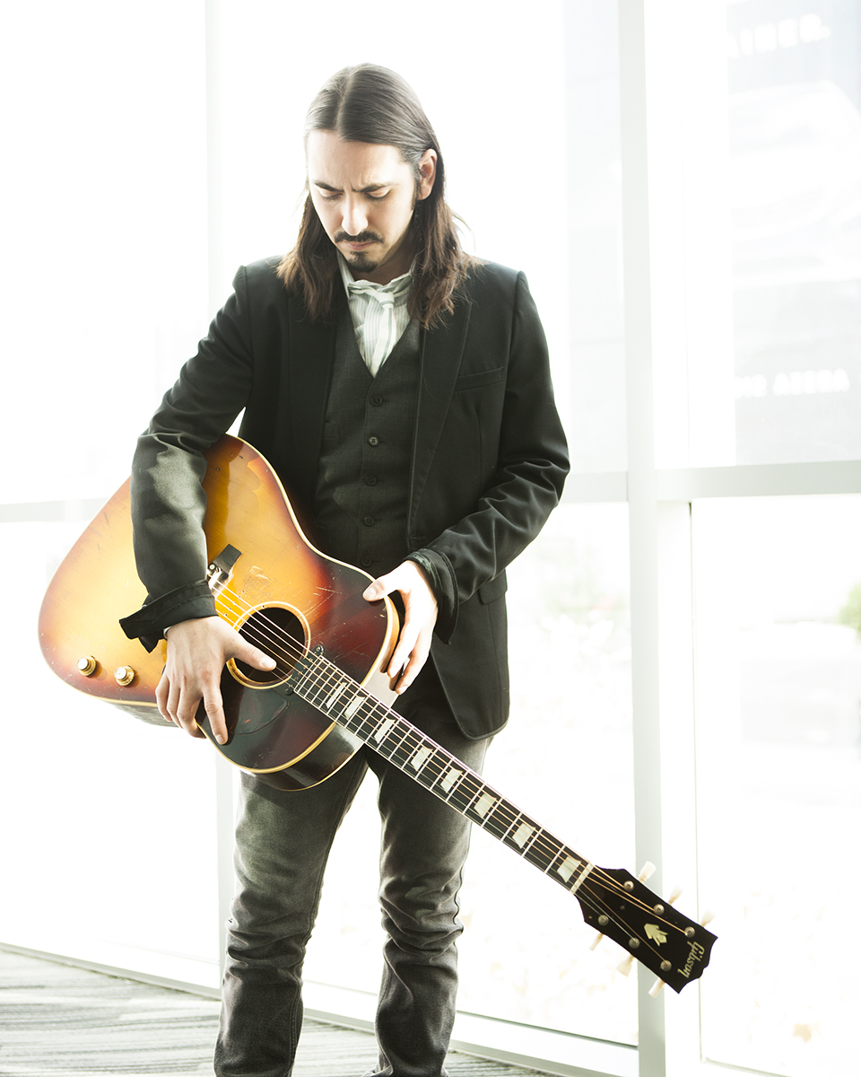 Dhani Harrison holding his father's Gibson J-160E.