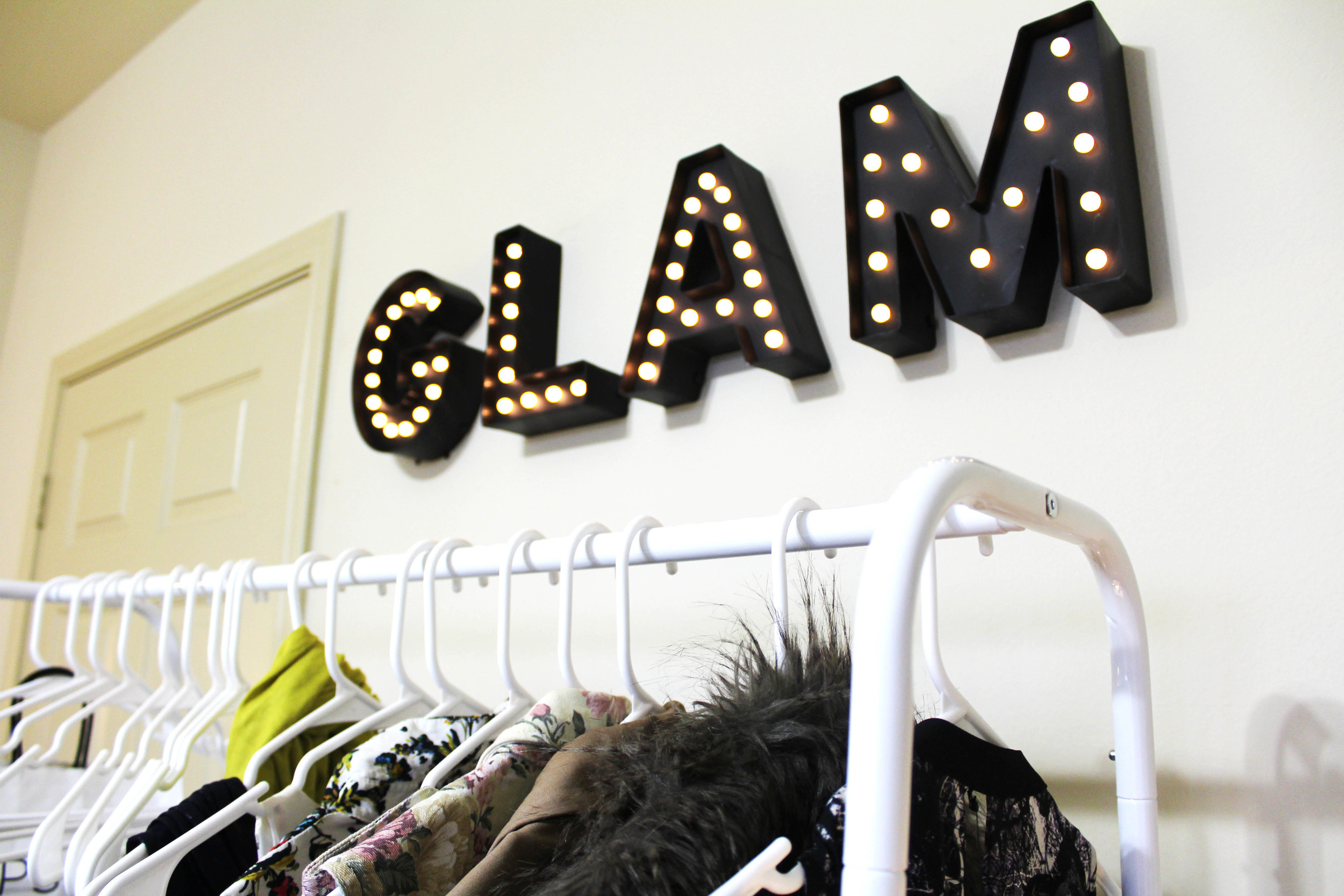 "I switched out my ""industrial"" rolling rack and replaced it with this super cute white one! It's the perfect way to show off your favorite wardrobe pieces and extend your closet. I added marquee letter lights above mine to spell ""GLAM""."