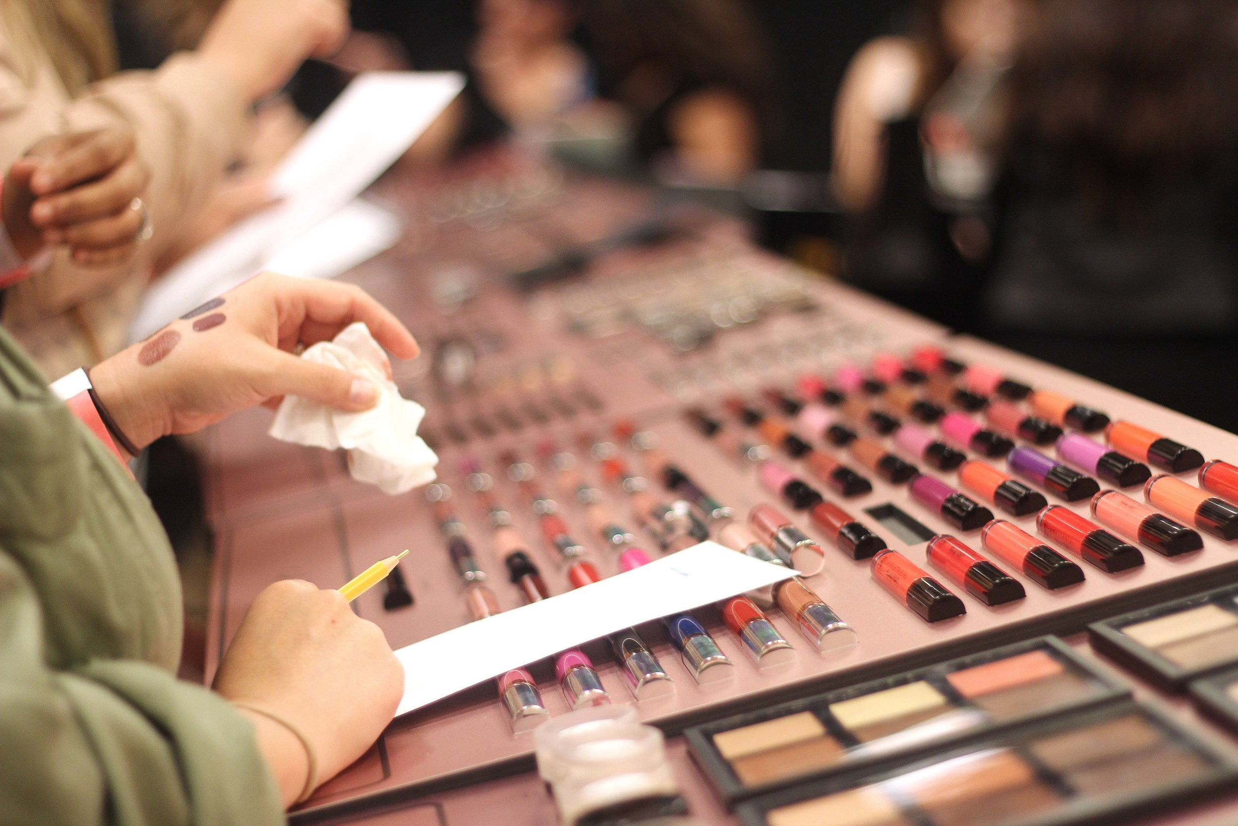 Attendees swatching liquid lipsticks at the Anastasia Beverly Hills booth.
