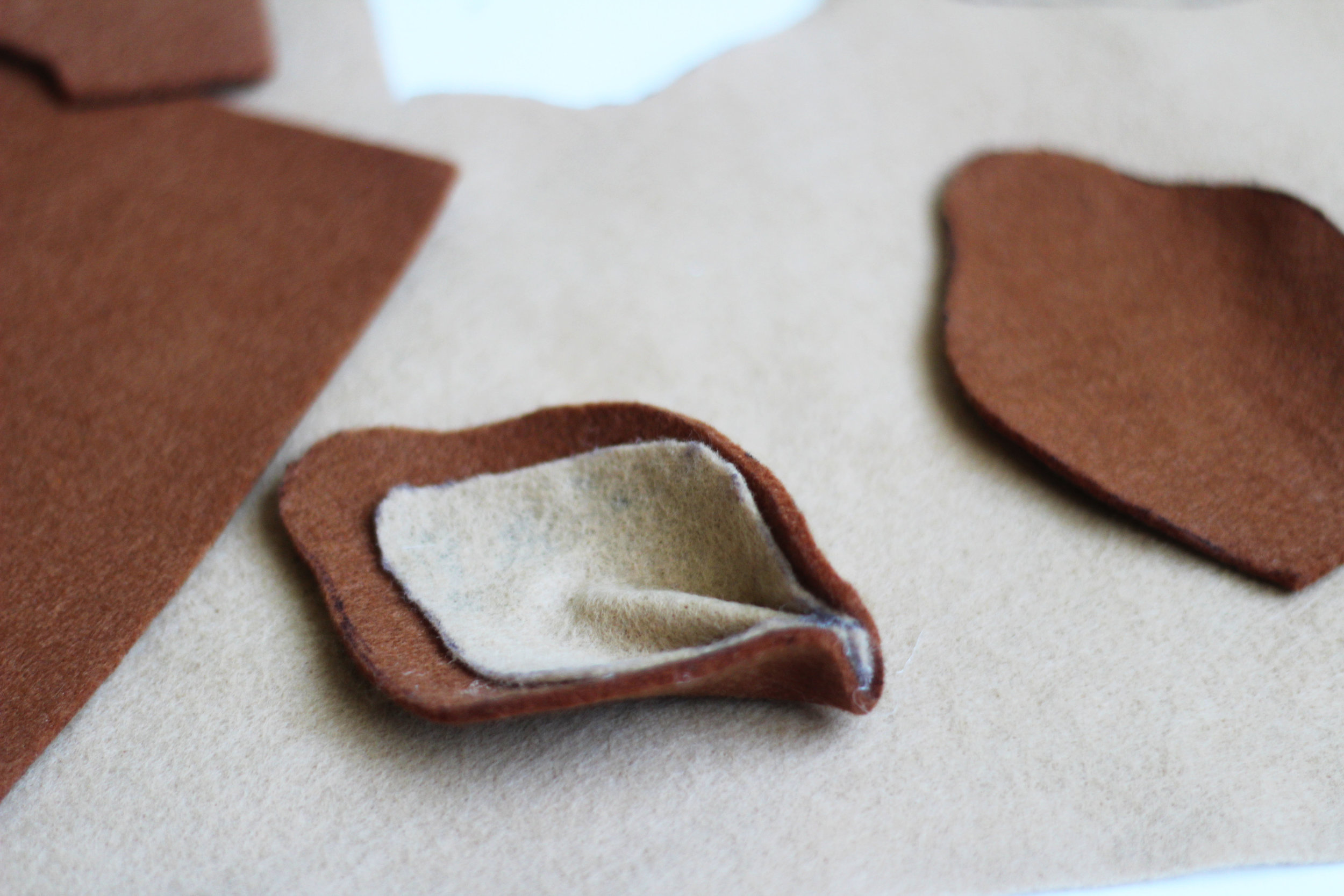 Use felt to create two ears for your headband, then use hot glue to attach them.