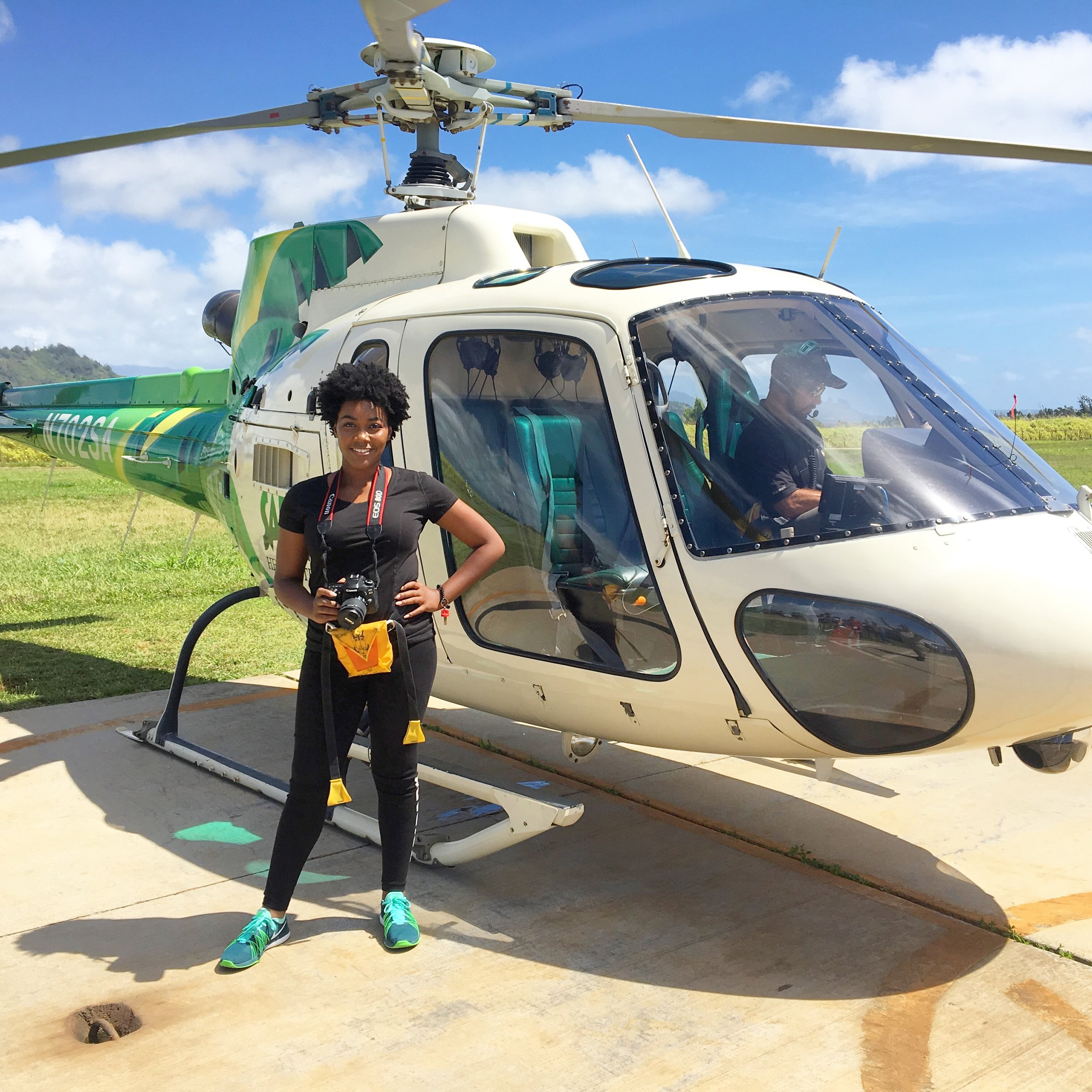 Me next to the helicopter after our tour with my camera. I got so many amazing photos!
