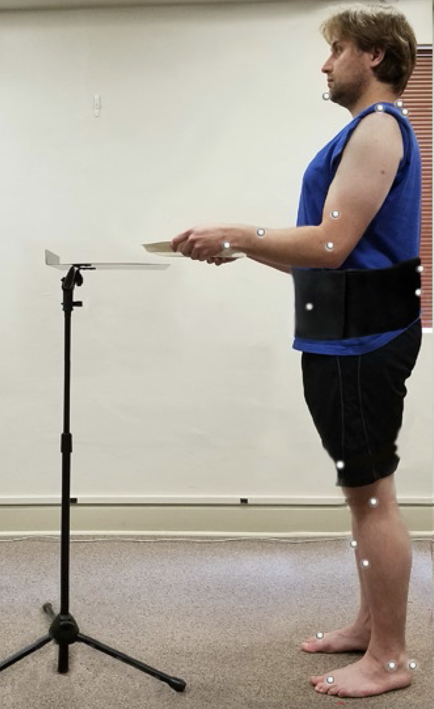 Figure 2: A study participant wearing reflective dots tracked by the 3D motion capture camera system. In the first task, participants walked 2 meters carrying a tray, and set it down at elbow height. The researchers began collecting data 3-seconds before the subject started walking. They were curious to see if forward head posture increased in anticipation of walking.