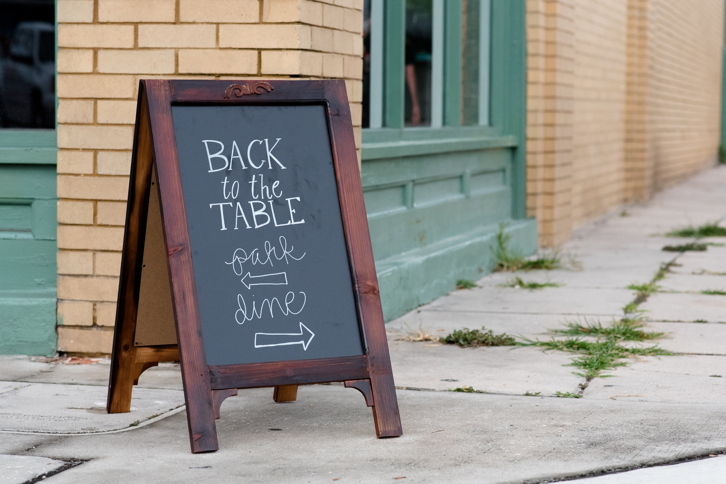 Simple and unassuming sign pointing guests in the direction of the undisclosed Back to the Table dining location