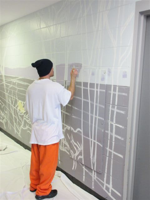 Beginning to paint a forest, down the hall from the YOU ARE LOVED mural at Bridgewater State Hospital.