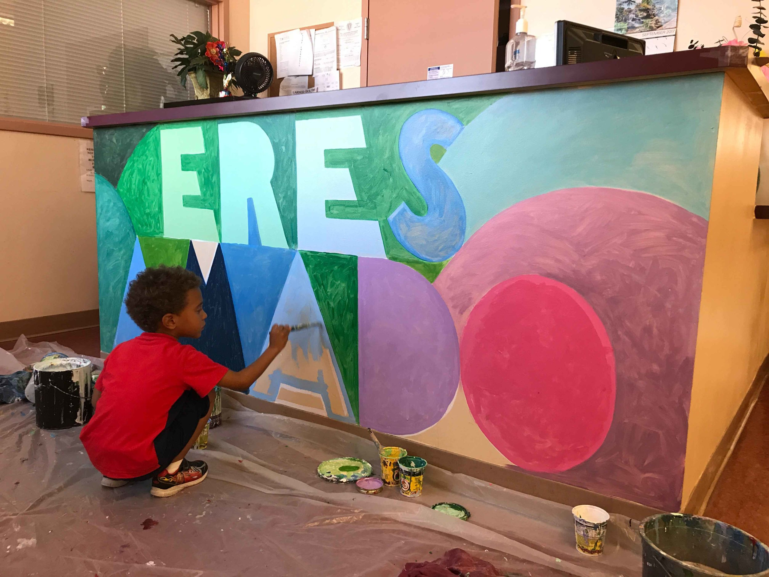 A young boy helps fill in ERES AMADO at the Mary Eliza Mahoney Family Shelter in Roxbury, MA