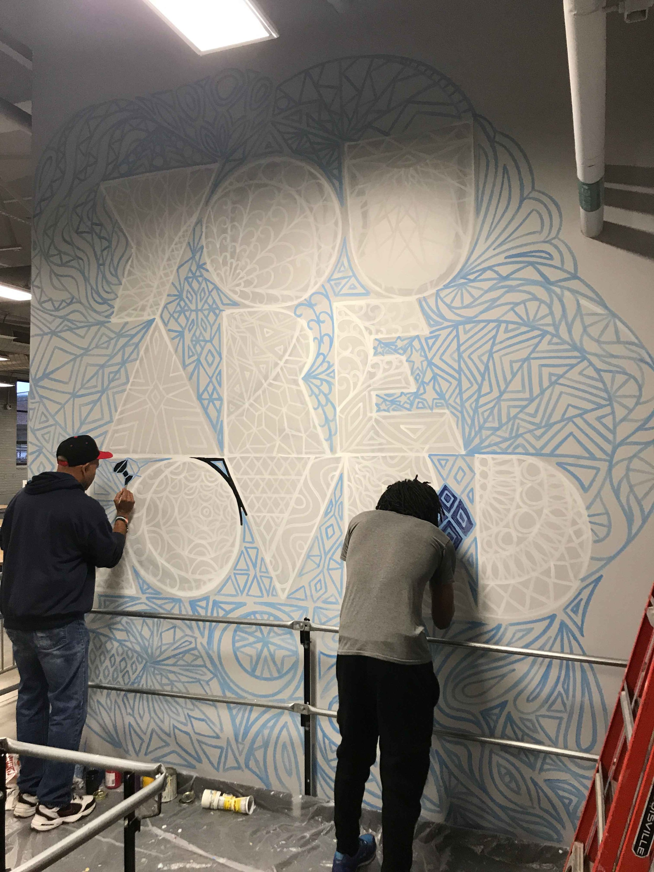 Residents work on an intricate YOU ARE LOVED design at the Southampton Street Shelter in Boston, MA