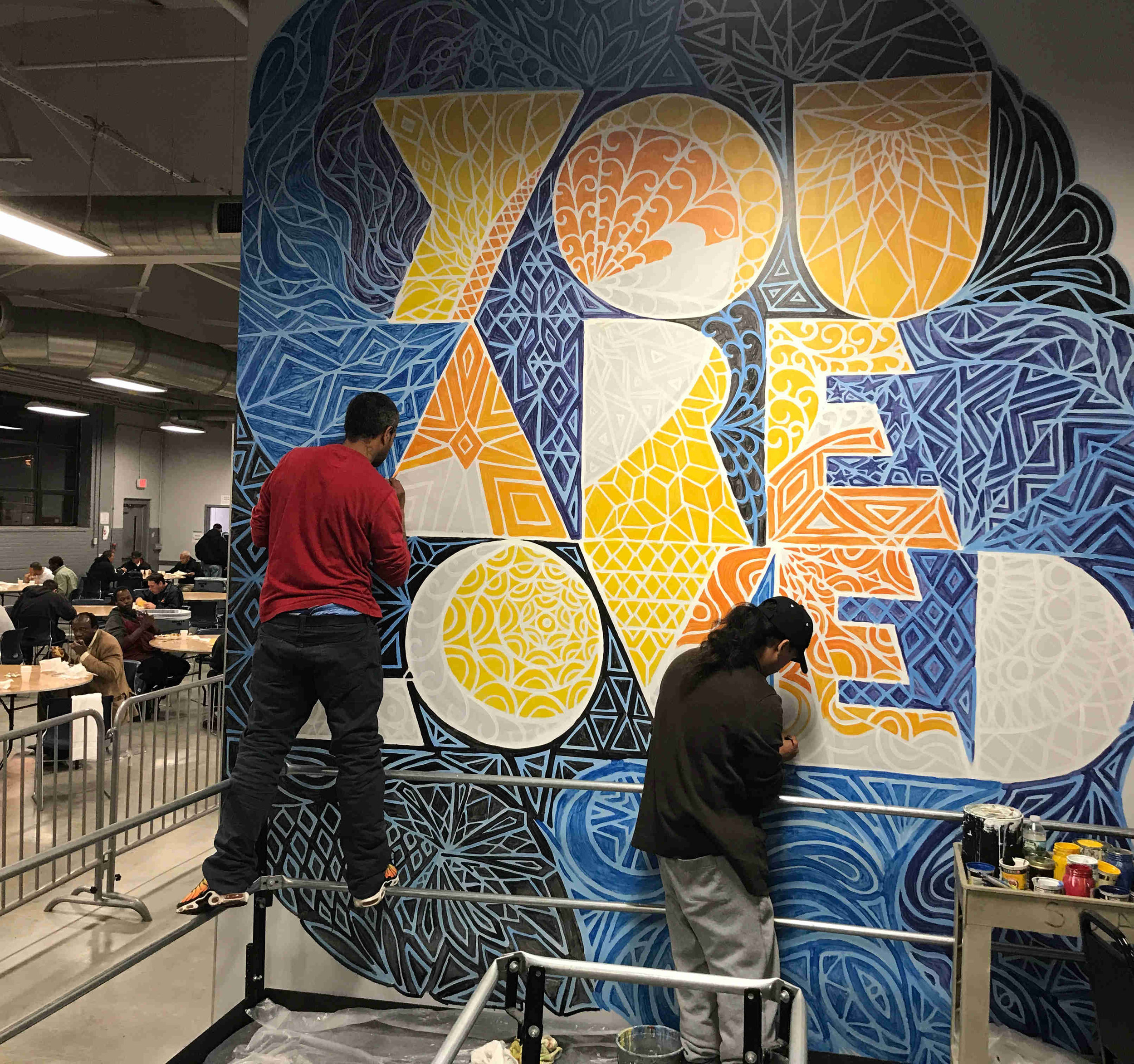 Residents help paint an intricate YOU ARE LOVED design at Southampton Street Shelter in Boston, MA. Each of the facility's 500+ residents sees this mural every day.