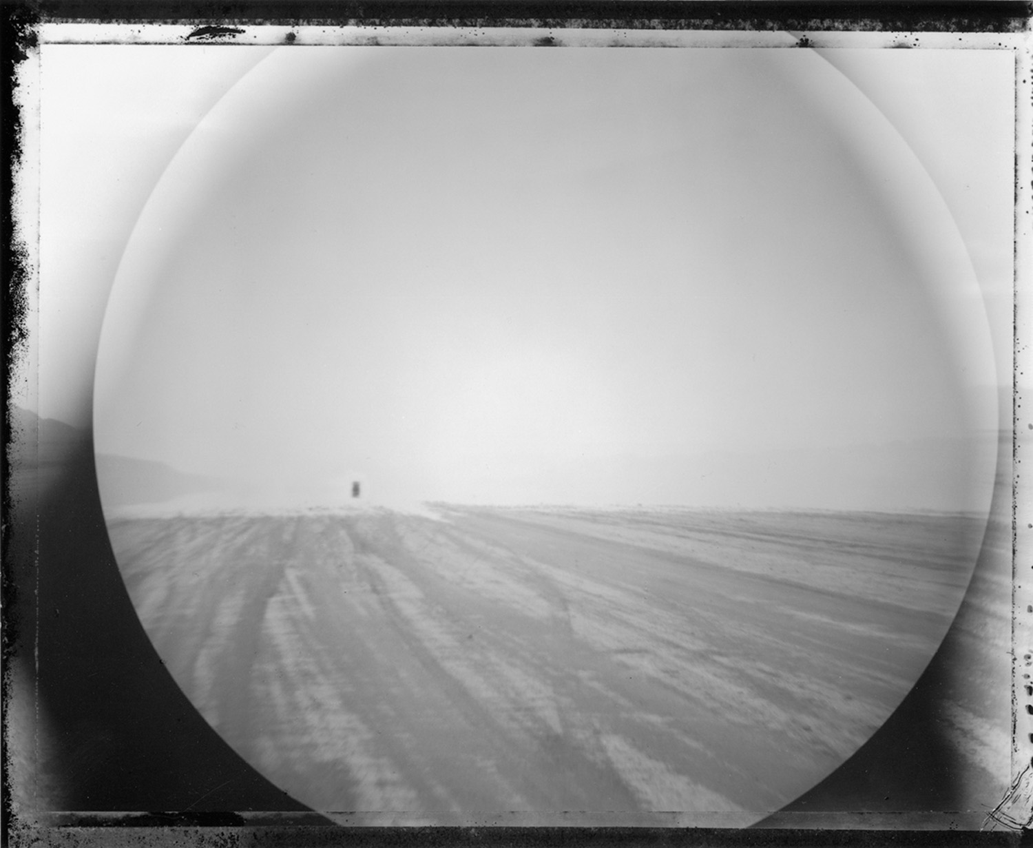 View through binoculars: truck two miles distant approaching through a mirage, 2000