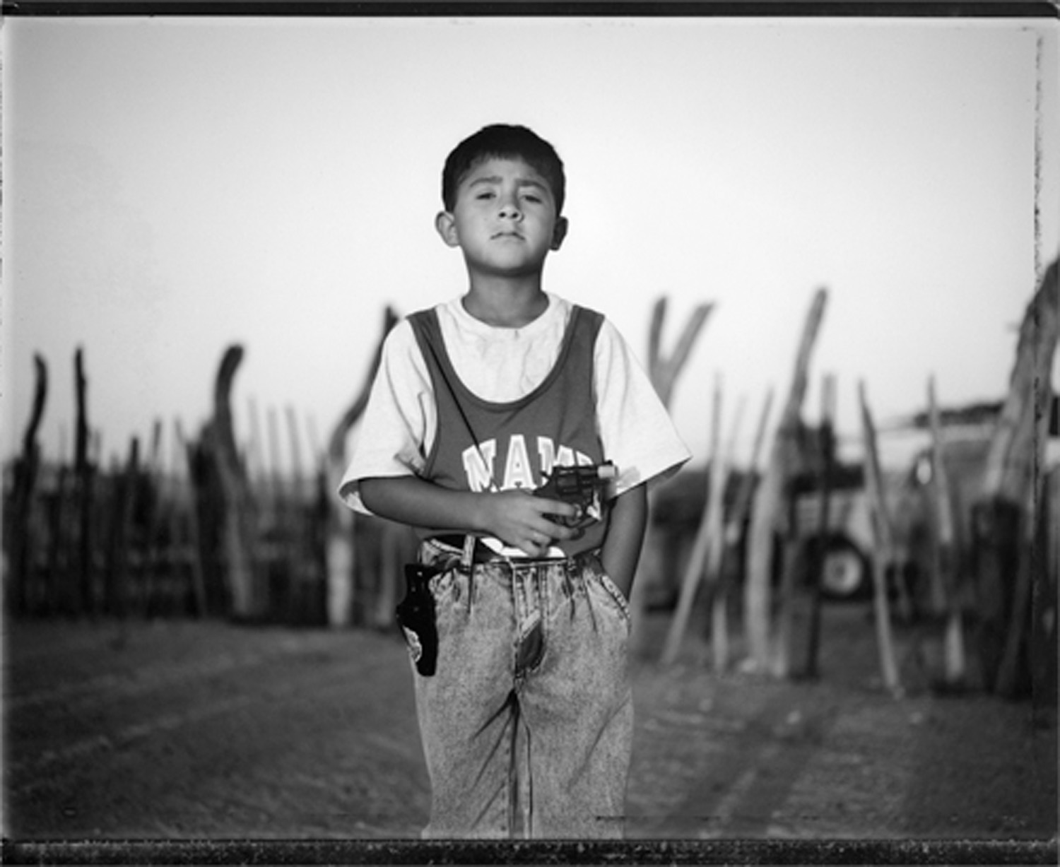 Boy with toy gun, border town, Mexico, 1993