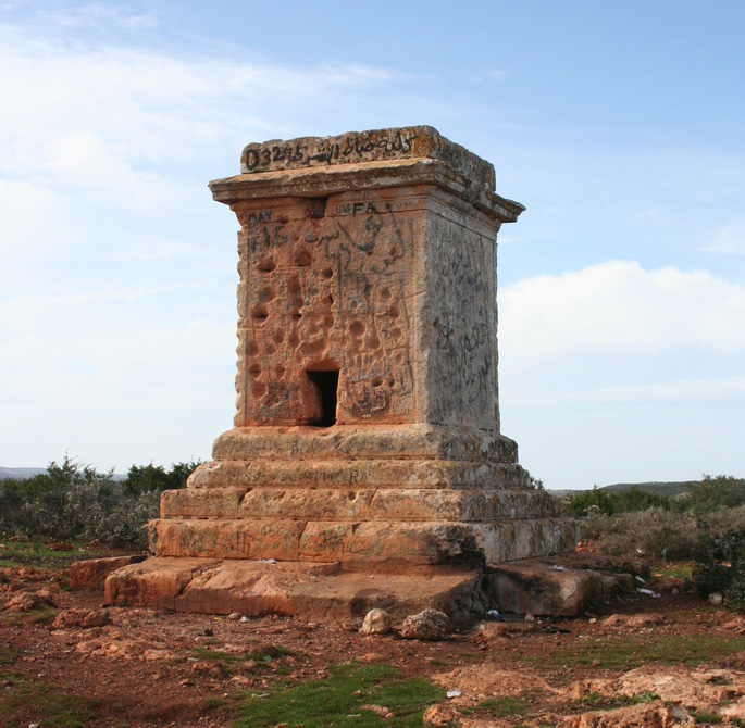 A tomb of the late Hellenistic or early Roman period in the Cyrenaican countryside. The pock-marks are the result of its use for target practice, probably in the 19th or 20th century AD; the spray-paint is more recent.