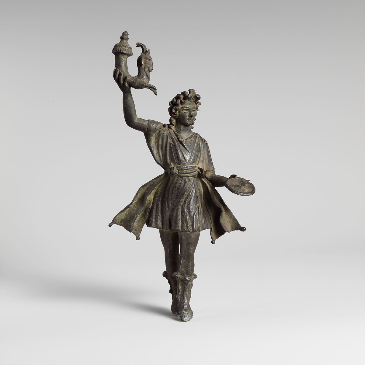 A singular lar, stepping forward in dance, with a rhyton is his right hand ( Met Museum )