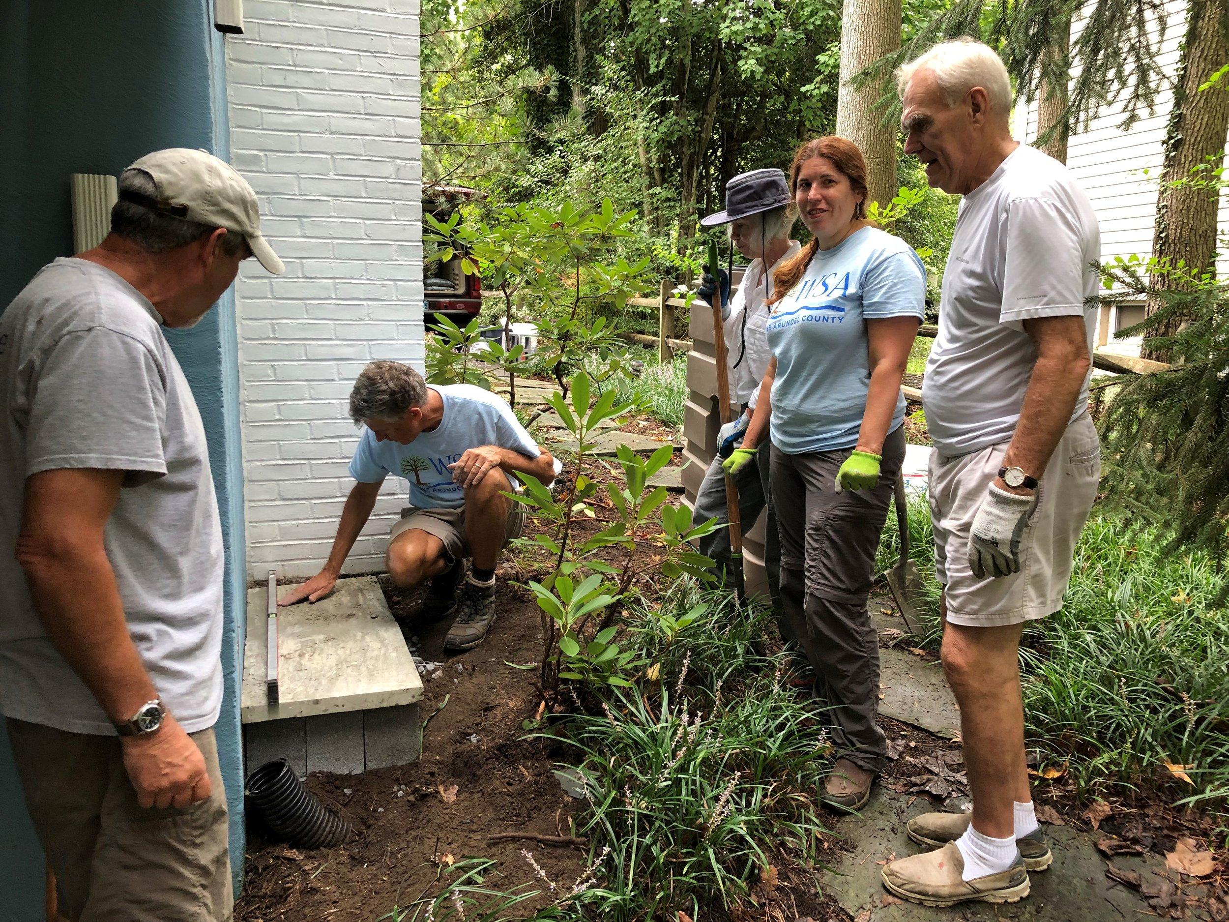 Kevin Green, Thomas Marston, Monica Maynard, Katie Matta and Marc Wirig install a rain barrel in Hillsmere.