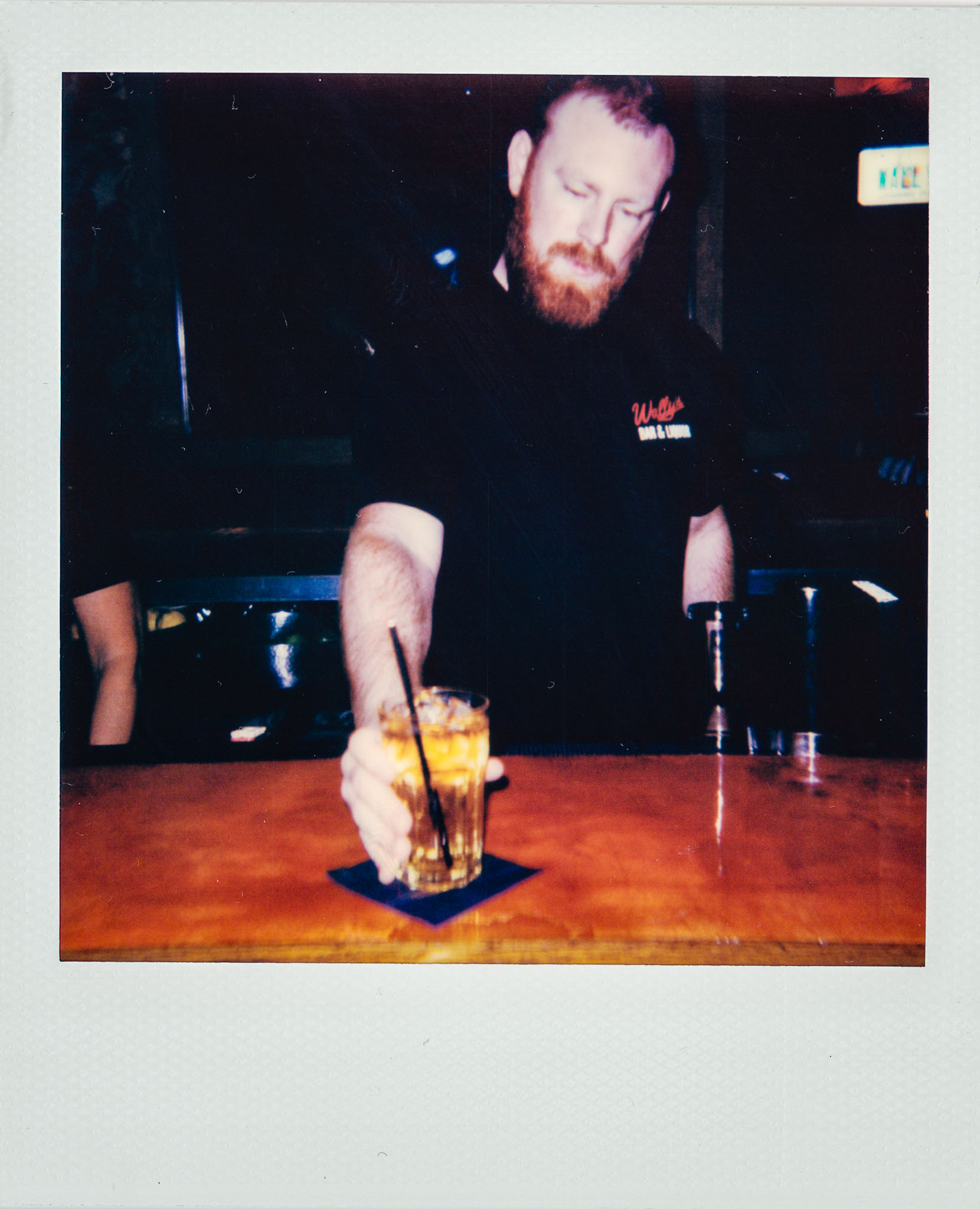 Redhead Bartender Serving a drink at Wallys Mills Avenue Liquors