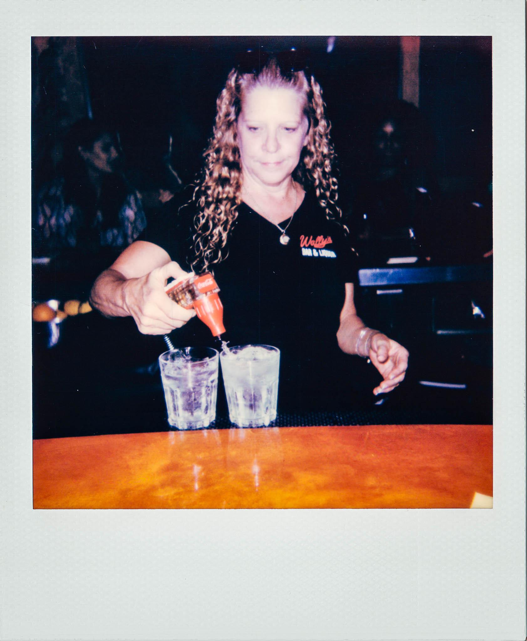 Female bartender making drinks at Wallys Mills Avenue Bar