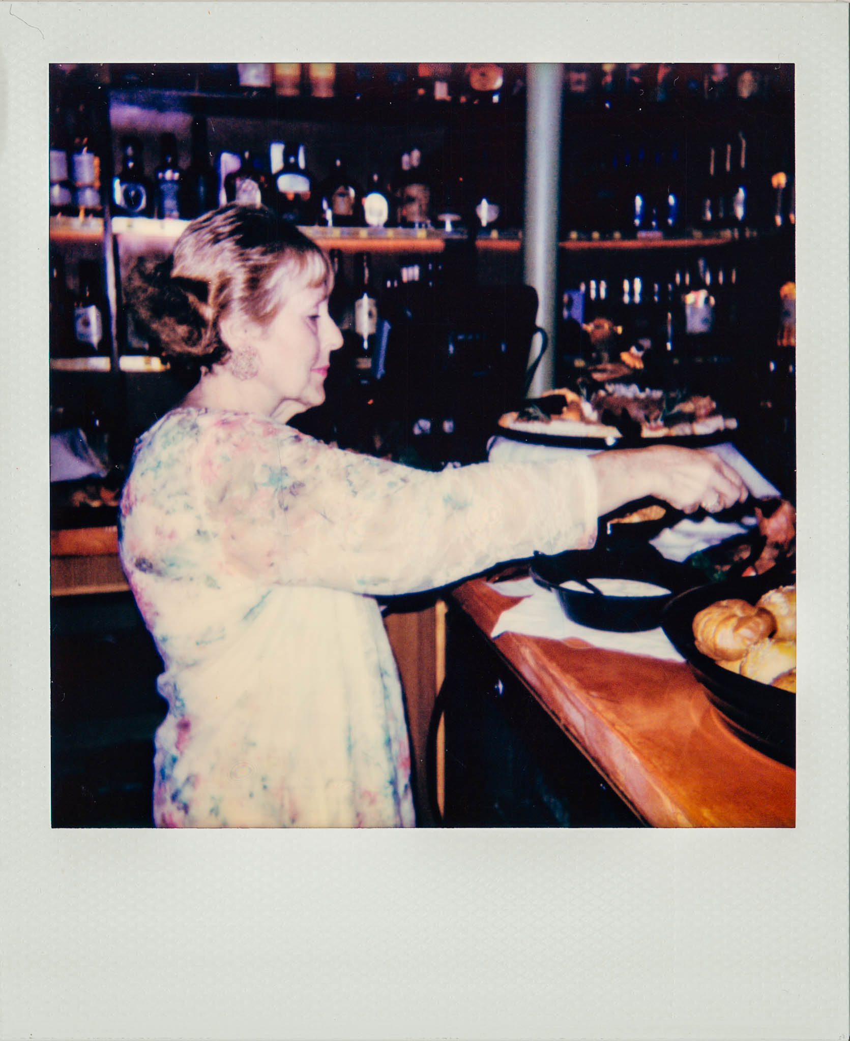 Linda Updike filling a plate with food at Wallys Mills Ave Liquors.