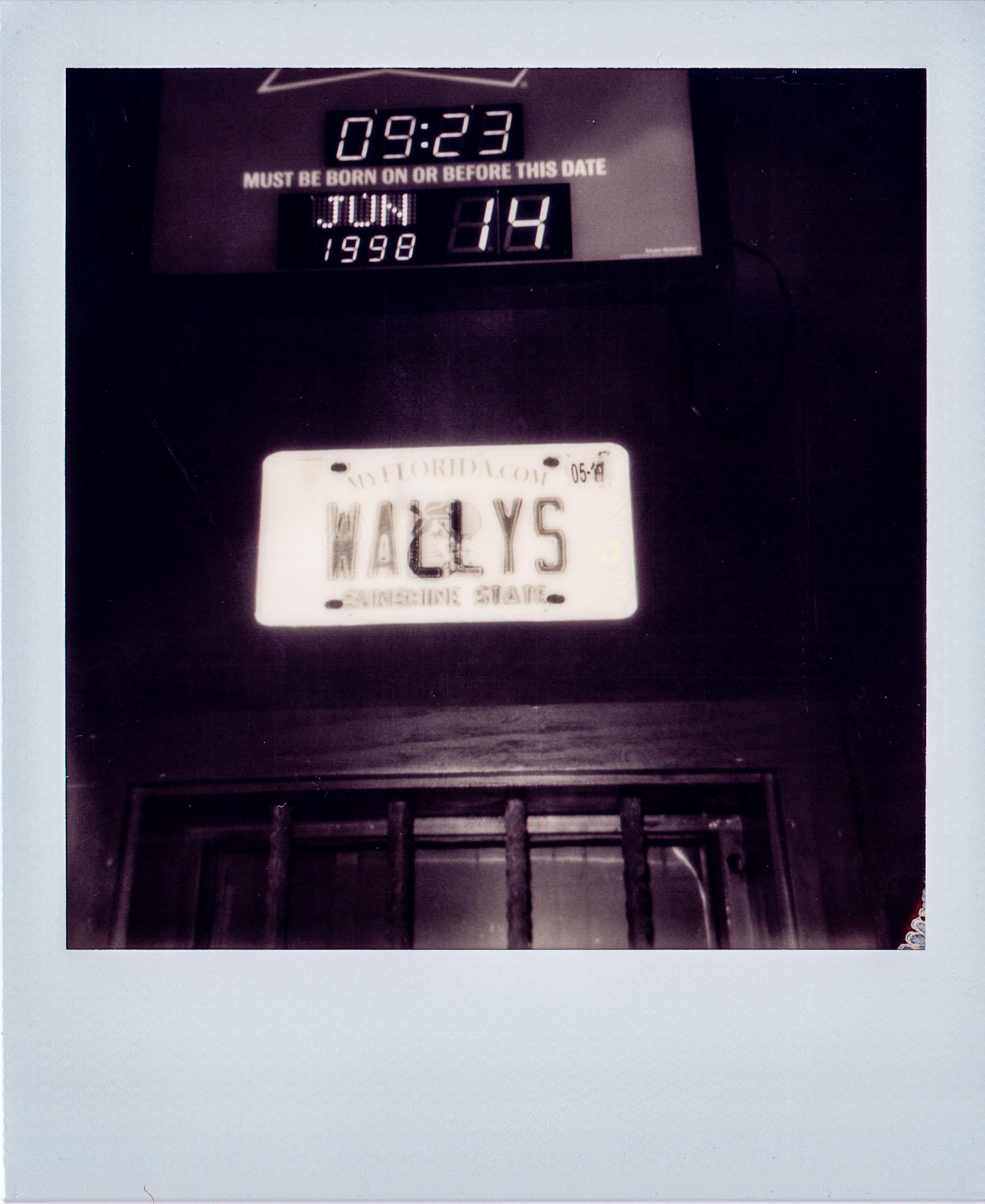 Wallys license hanging above the bar at Wallys Mills Avenue Liquors