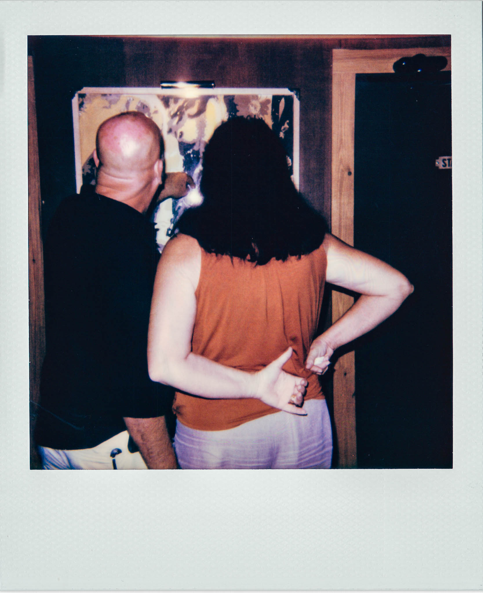 Couple looking at print of nude ladies at Wallys Mills Avenue Liquors