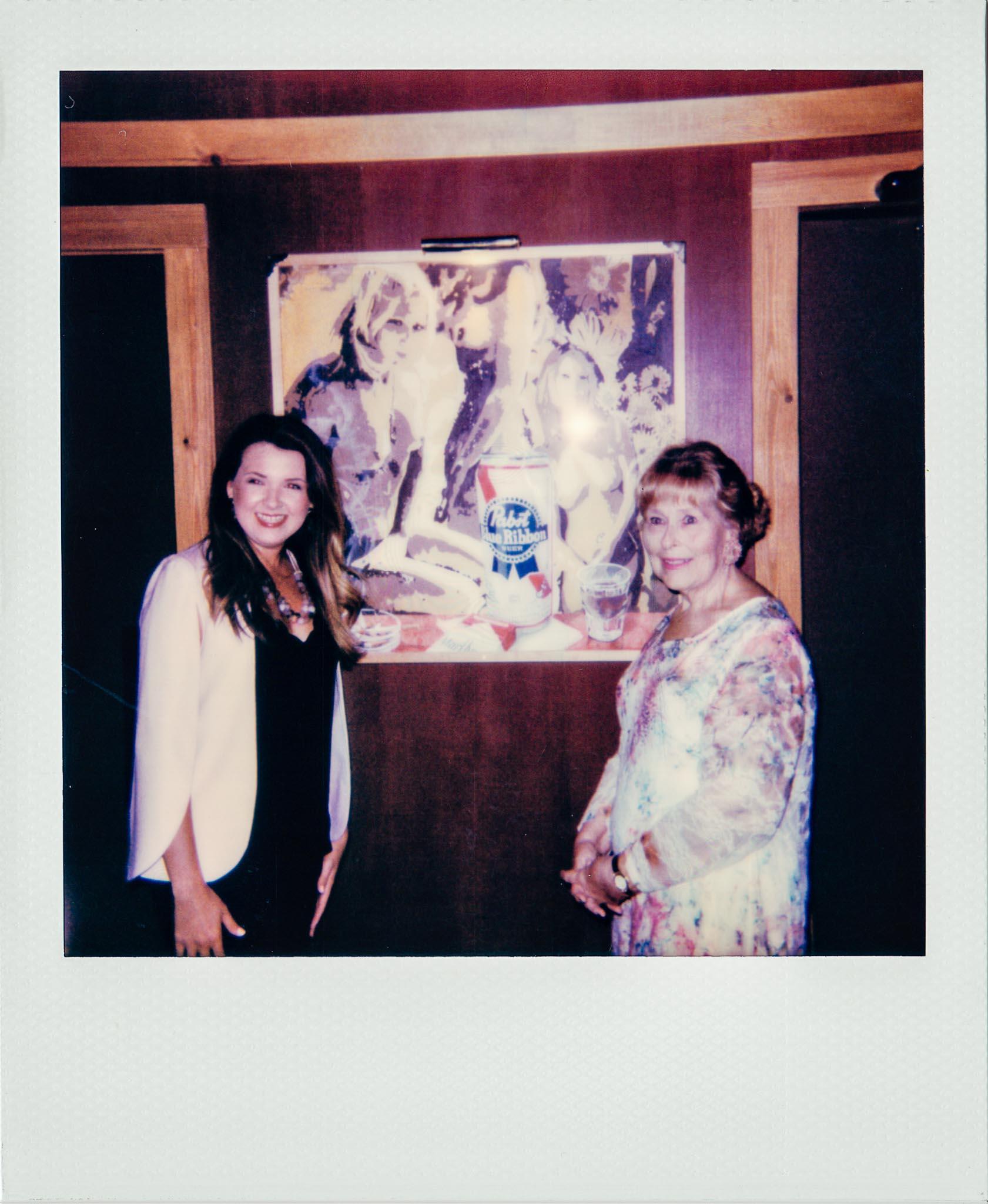Linda Updike and Lauren Ferriola posing in front of Wallys Nude Wall paper